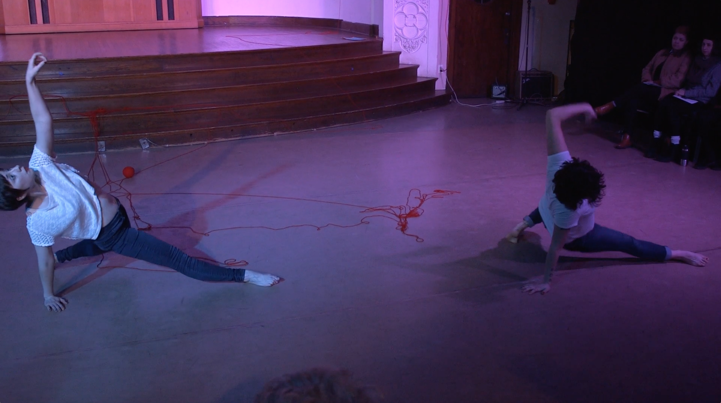 "Image: Maggie Robinson and Allison Sokolowski performing in ""I Am."" The dancers suspend themselves off the floor in variations of the same pose, as if pausing while sliding into a split. Allison reaches and looks up at the ceiling and Maggie reaches and looks toward the audience. Around them on the floor are strands of red yard. The lighting is dim and cool, with purple highlights. Audience members are slightly visible in the foreground and background. Still from a video by John Borowski."
