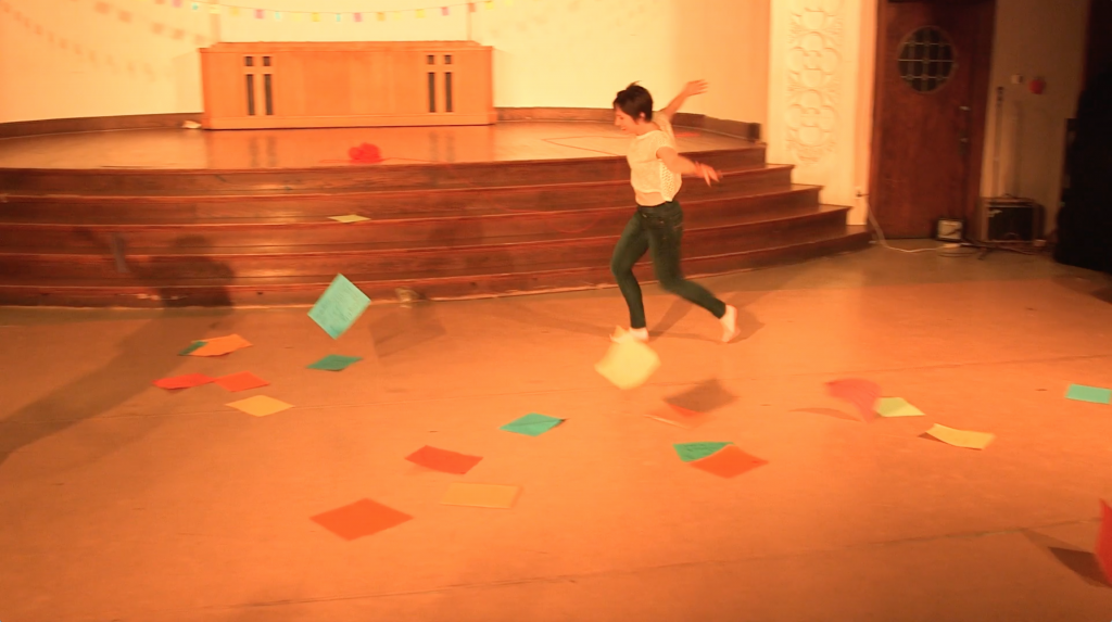 "Image: Allison Sokolowski performing in ""I Am."" In this long shot of the performance area, Allison runs with arms spread as colorful pieces of paper fall through the air and onto the floor. A shadow of Maggie in a similar pose (off-camera) is slightly visible. The performance space is bathed in warm yellow-orange light. Still from a video by John Borowski."