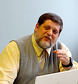 Image: Photo of Arnie Aprill, arts and learning consultant with Envisioning Justice. Arnie Aprill turns toward the camera as he speaks while gesturing with his left hand. He is wearing a light yellow shirt with a gray sweater vest and light colored tie and has a laptop open in front of him. Photo courtesy of Arnold Aprill.