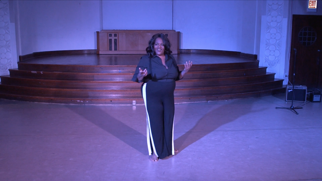 "Image: Jae Green performing in ""Wax."" Jae smiles brightly at the audience, her arms bent at the elbows with palms facing up. She stands in the middle of the floor, her shadow cast toward the stage in two directions. The lighting is dim and cool (blue-purple). Still from a video by John Borowski."