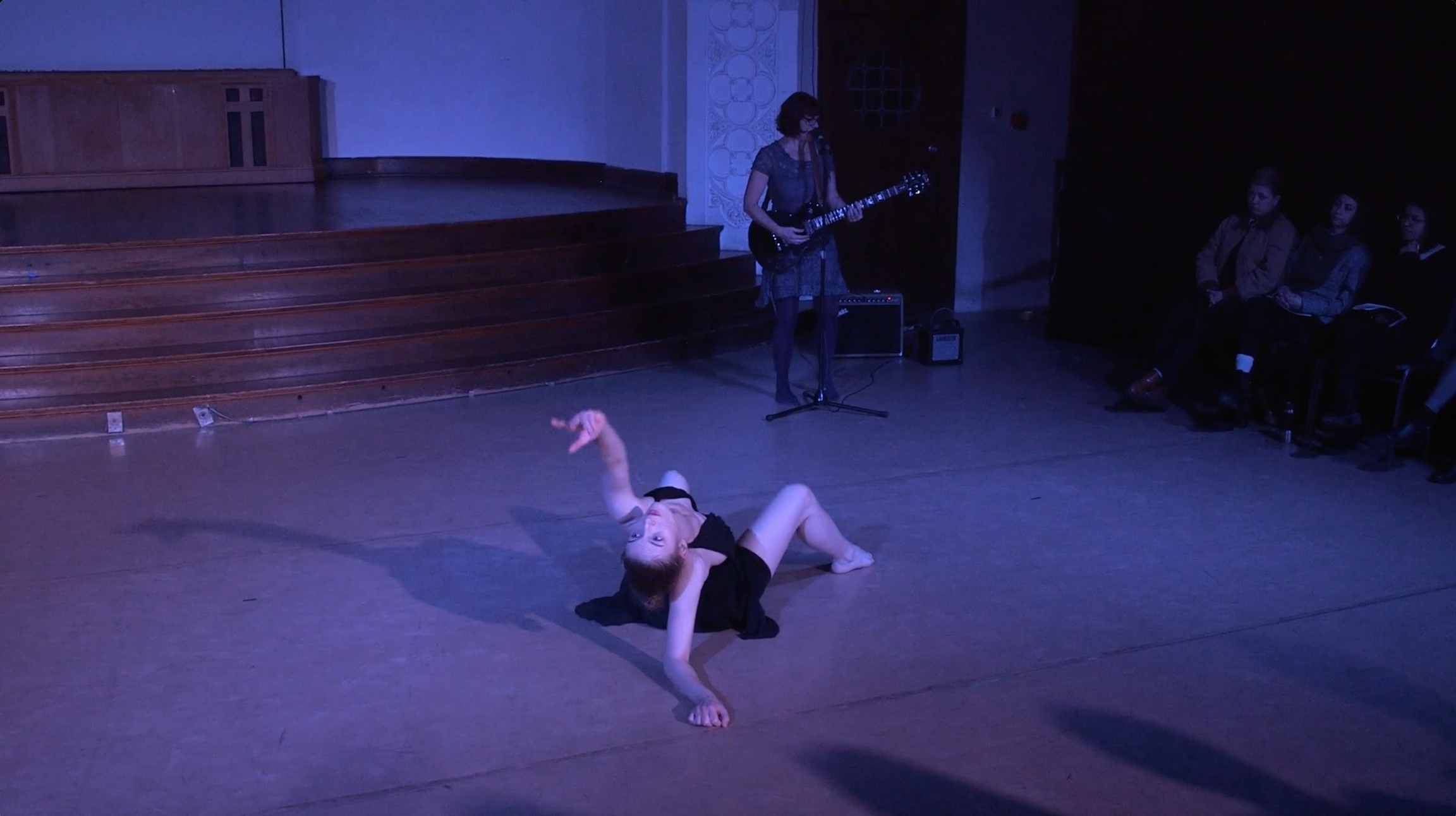 "Image: Carly Broutman and Michelle Shafer performing in ""Wax."" In the back corner, Michelle plays electric guitar and sings into a microphone on a stand. Carly is on the floor, body and feet angled toward Michelle, while leaning back on one elbow, reaching and looking past the camera. The audience is partially visible in the background and via cast shadows in the foreground. The lighting is dim and cool (blue-purple). Still from a video by John Borowski."