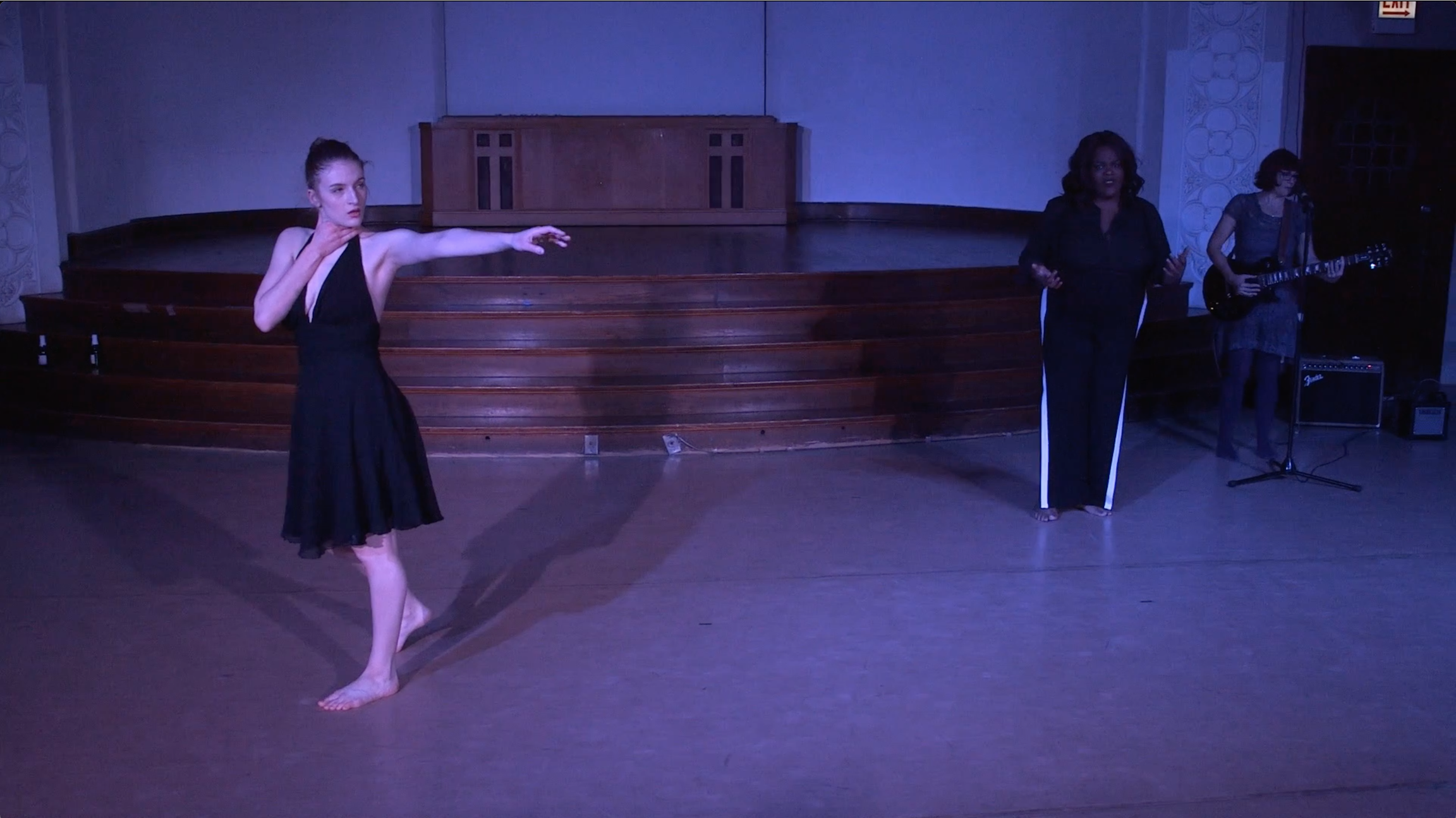 "Image: Carly Broutman, Jae Green, and Michelle Shafer performing in ""Wax."" In the foreground, Carly steps forward, with one hand on her throat and her other arm stretched across the frame, her face looking that way too. In the back corner, Jae speaks, palms up in a gesture, as Michelle plays electric guitar. The lighting is dim and cool (blue-purple). Still from a video by John Borowski."