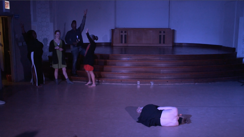 "Image: Carly Broutman and Jae Green performing in ""Wax."" Carly lies on the floor in a ball in the foreground, her back to the camera. In a far corner, Jae and three guests celebrate, smiling, yelling, holding beverages, and/or throwing arms in the air. The lighting is dim and cool (blue-purple). Still from a video by John Borowski."
