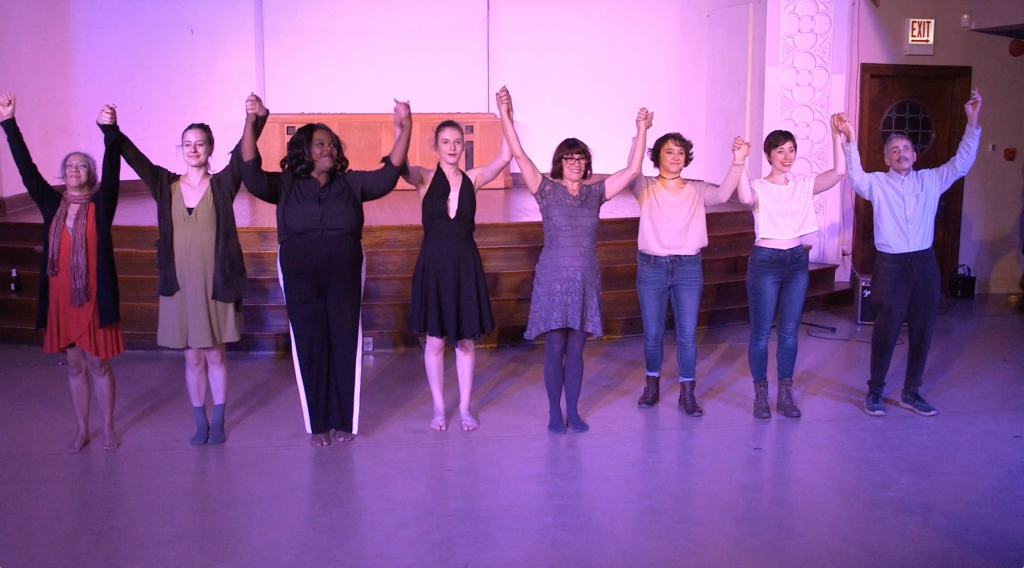 Image: The curtain call, showing all performers from the Body Passages culminating event. The performers stand in front of the stage, smiling and holding hands, arms up in the air. The lighting is pink-purple. Still from a video by John Borowski.
