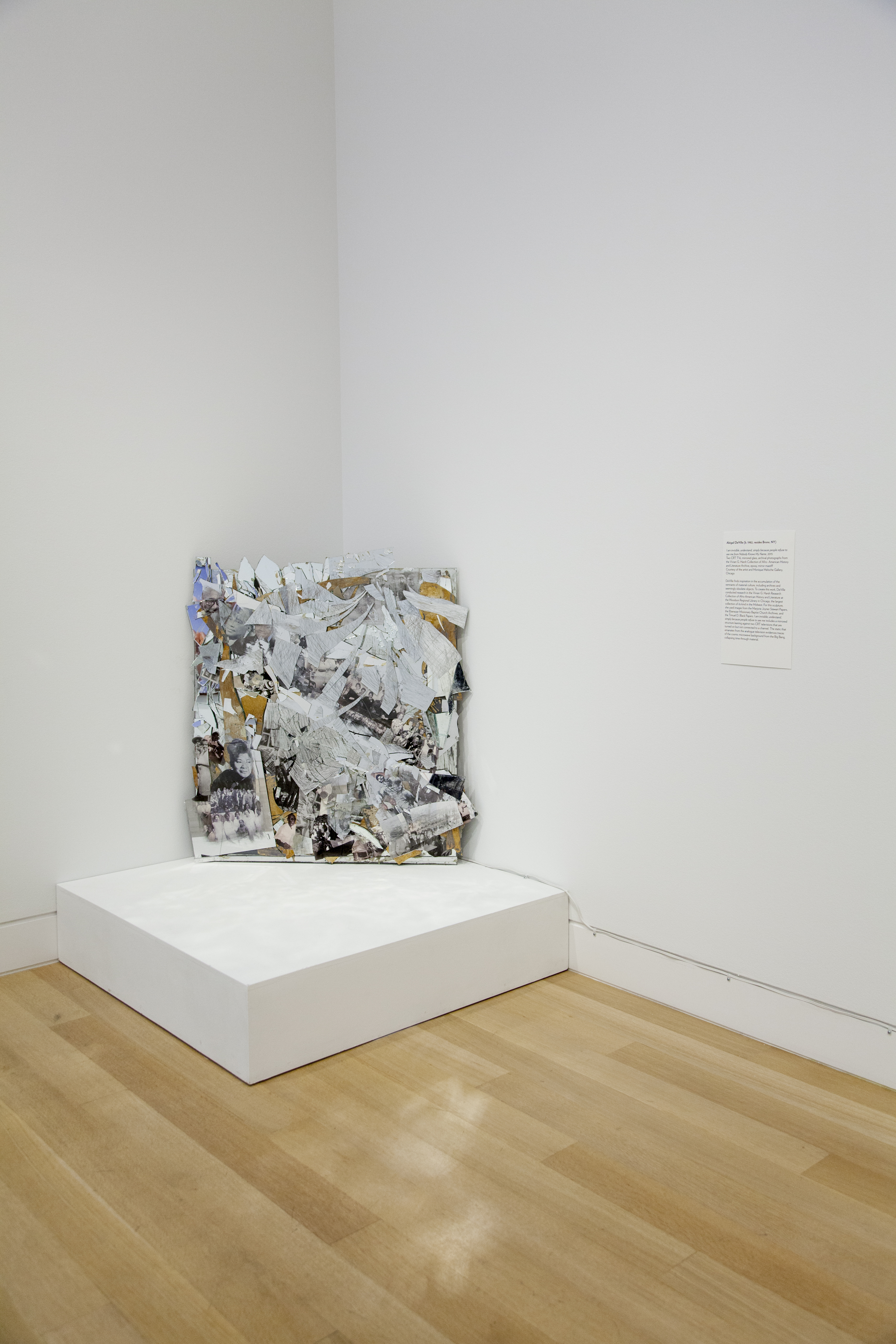 Image: Abigail DeVille, I am invisible, understand, simply because people refuse to see me from Nobody Knows My Name, 2015 [installation view]. A collage of shattered glass and imagery covers a gutted television leaning against the corner of a room. Image courtesy of DePaul Art Museum.