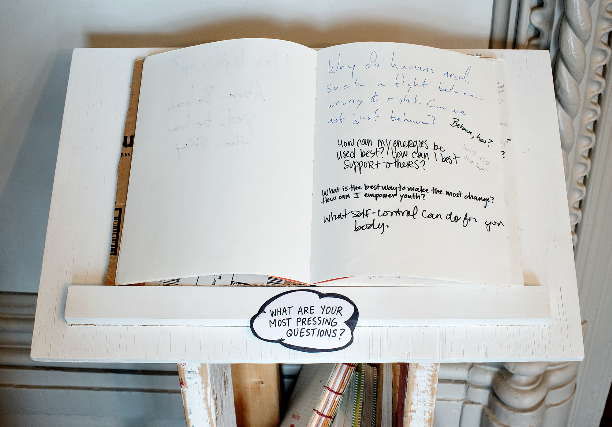 """Image: Detail view of a book and prompt set on one of the mobile pedestals in the Everything on Wheels series, placed in one of the downstairs rooms at Hull-House. The prompt says """"what are your most pressing questions?"""", and people have written answers such as """"How can my energies be used best? How can I best support others?"""", or """"What is the best way to make the most change? How can I empower youth?"""" Photo by Greg Ruffing."""