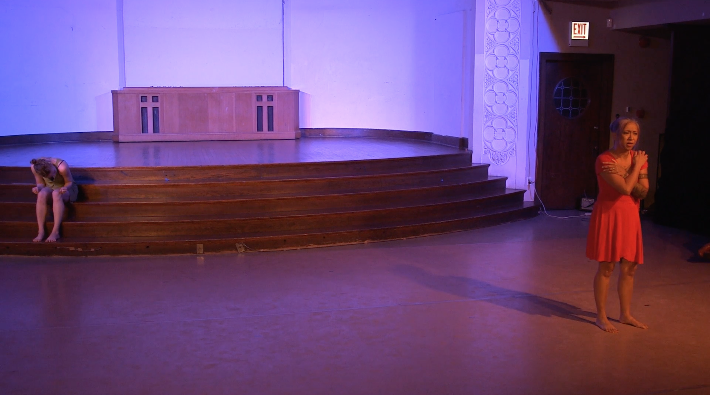 """Image: Maxine Patronik and Lani T. Montreal performing in """"Blood Memory."""" Lani is in the right foreground of the image. She stands near the middle of the floor, speaking, with her forearms crossed and her hands touching her shoulders. In the back left, Maxine sits on a stage step, folding her torso over her quads and clenching her fists. The lighting is dim and cool (blue-purple). Still from a video by John Borowski."""