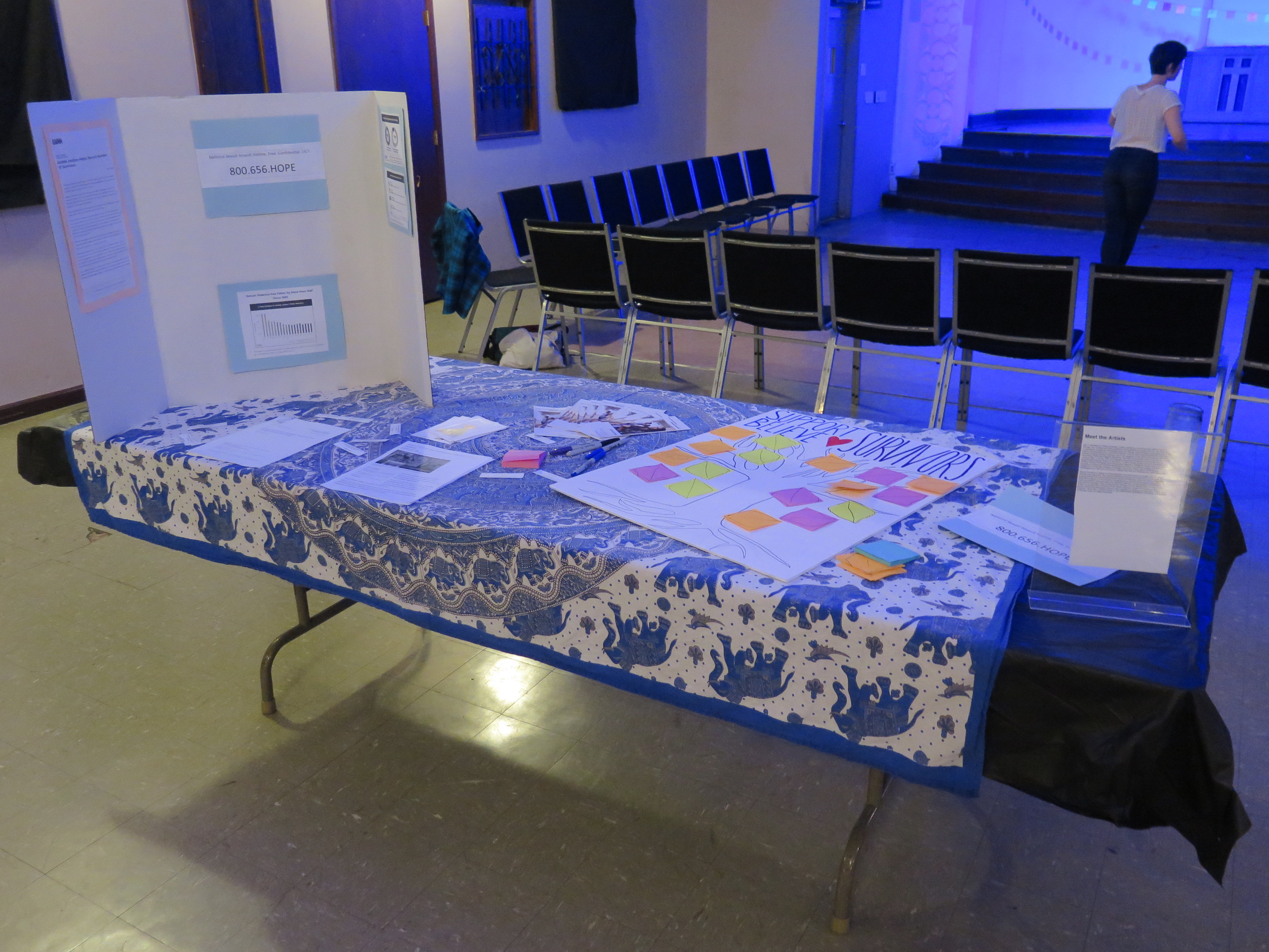 "Image: The interactive display related to Lani T. Montreal and Maxine Patronik's performance ""Blood Memory,"" at the Chicago Danztheatre Auditorium as part of the Body Passages culminating event. In the foreground, a table is covered with blue-and-white elephant-print cloth, a tri-fold posterboard, and various papers, including a large one that reads ""SUPPORT BELIEVE"