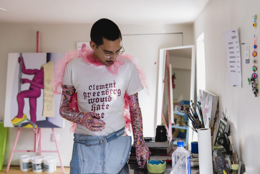 "Image: The artist is in their studio wearing pink and purple gloves. They are wearing a white shirt with text that says ""Clement Greenberg would hate me"" and looking down at a table. In the background there is a painting on an easel with a pink figure wearing crocs. Photo by Ryan Emdund Thiel."