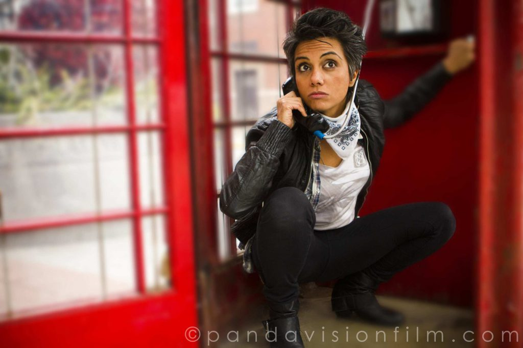 "In this photo, Fawzia (as the character Kam Kardashian) crouches low inside a red phone booth. Plants, a building, and daylight beyond are visible through the phone booth's glass windows and open door. Fawzia (as Kam) wears a black leather jacket, white shirt, tight black pants, and black boots, as well as a white and black bandana around her neck. She holds the phone receiver to her face and looks off-camera with eyebrows raised. In the bottom right-hand corner of the image it reads ""(c) pandavisionfilm.com."""