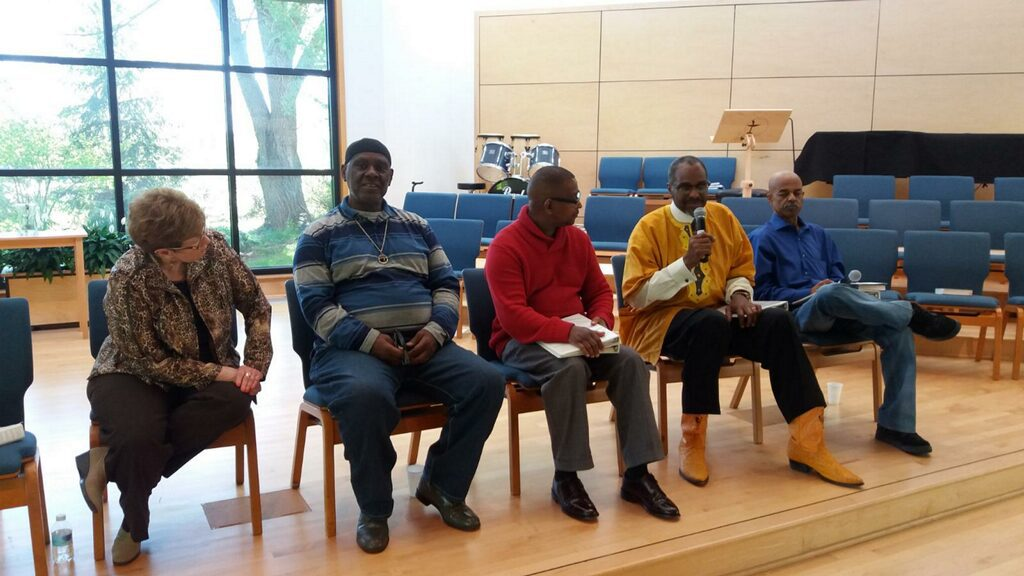Image: Five people sit in chairs on a stage. One man is holding a microphone. Photo courtesy of Michael Fischer.