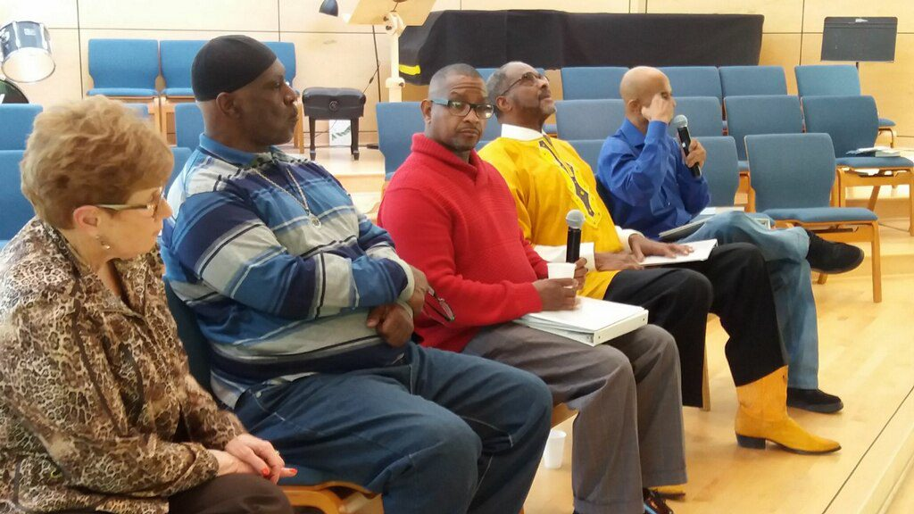 Image: Five people sit in chairs on a stage. Two of the men are holding microphones, responding to audience questions. Photo courtesy of Michael Fischer.