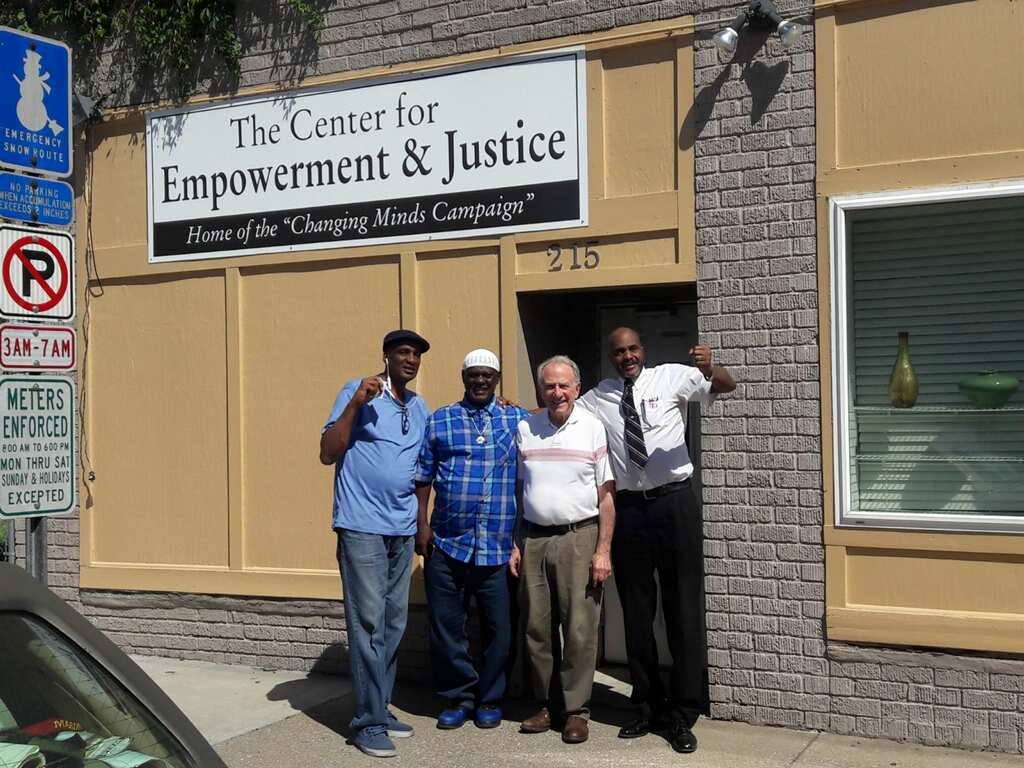 "Image: Danny Franklin and three other men stand on the sidewalk outside ""The Center for Empowerment & Justice: Home of the 'Changing Minds Campaign.'"" Photo courtesy of Michael Fischer."