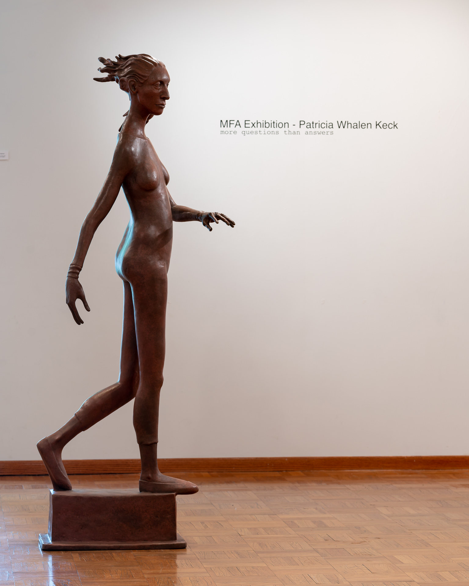 """Image: Patricia Whalen Keck """"The Pedestrian"""" Bronze. A large sculpture of a woman in a position that suggest she is walking or crossing across the space. The show title of the exhibition is seen on the wall in the background. Image courtesy of the artist"""