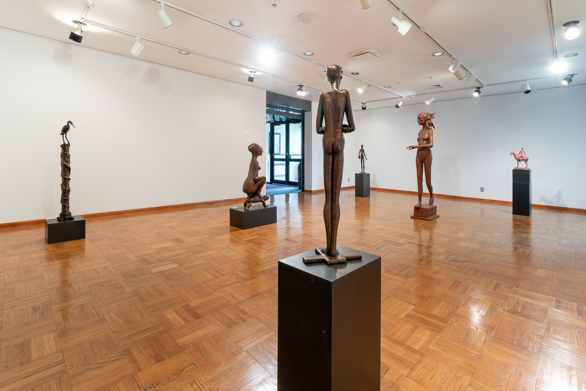 """Image: Installation shot of """"More Questions than Answers"""" Several sculptures are placed around a brightly lit gallery space. Most of them standing with one kneeling figure on the left. Photo courtesy of the artist."""
