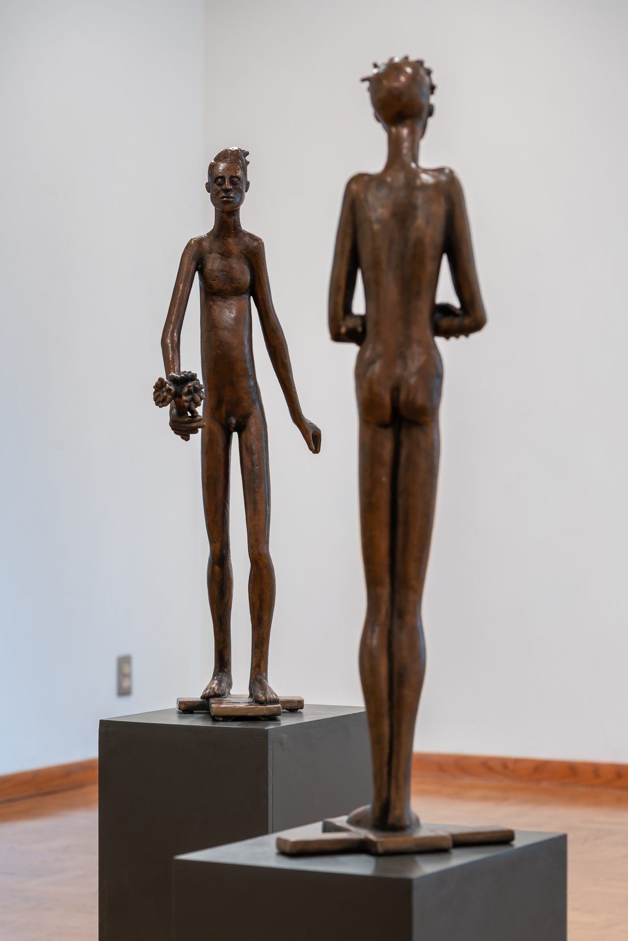 Image: Two of Keck's sculptures stand facing each other. A male figure holding flowers faces the viewer in the background while the backside of another sculpture is visible in the foreground. Image courtesy of the artist herself
