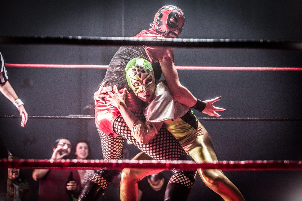 "In this still from the film ""Signature Move,"" Zaynab (played by Fawzia Mirza) wrestles lucha libre style with Ragina Cruz (played by Molly Callinan). Zaynab faces the camera, crouching, leaning into Ragina, and gripping Ragina by the hips. Ragina's body is angled away, with right arm outspread and hand open, as if caught by surprise. Zaynab wears a green, gold, and black lucha libre mask; a shiny, stretchy, full-length bodysuit that is gold and black; and a small silver cape. Ragina wears a red and black lucha libre mask; a black mesh and shiny red top with shiny red bottoms; and black fishnets, boots, knee pads, and accessories. In the foreground and background, the ring's black and red ropes are visible. A few spectators cheer in the lower left-hand corner, and a referee's arm enters the frame from the left. The frame's edges are slightly feathered and dark."