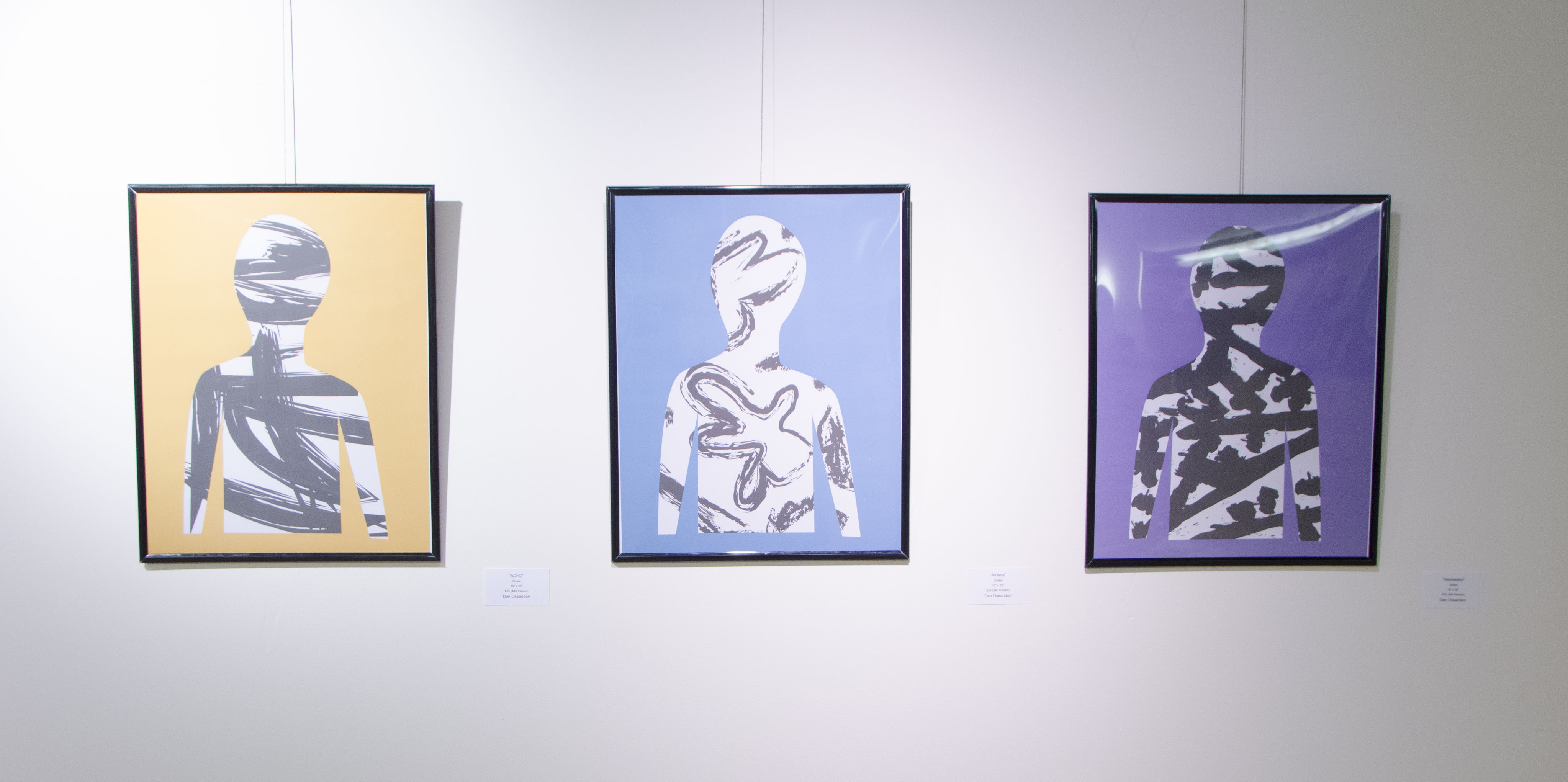 """Three works by EAC member Dan Ossandon """"Depression"""", """"Anxiety"""" and """"ADHD"""" All three are framed giclee prints."""