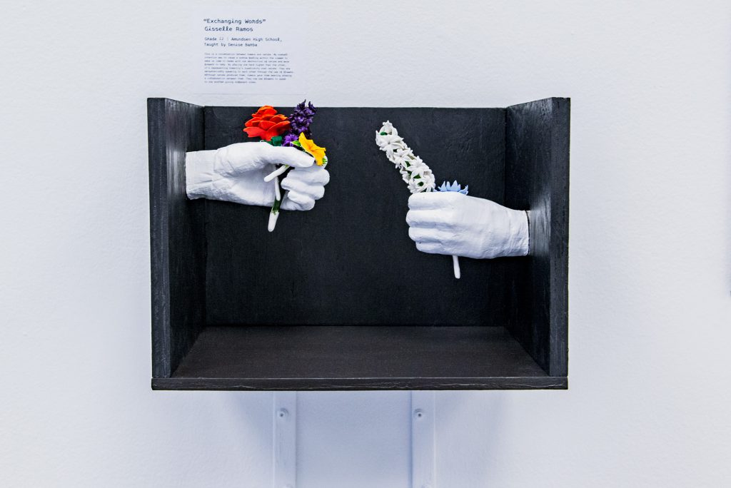 "Image: Gisselle Ramos, ""Exchanging Words"". A black wooden box containing white porcelain hands outreached toward one another, each holding delicate flowers. The hand on the left is positioned higher than the right. Photo by Ryan Edmund."