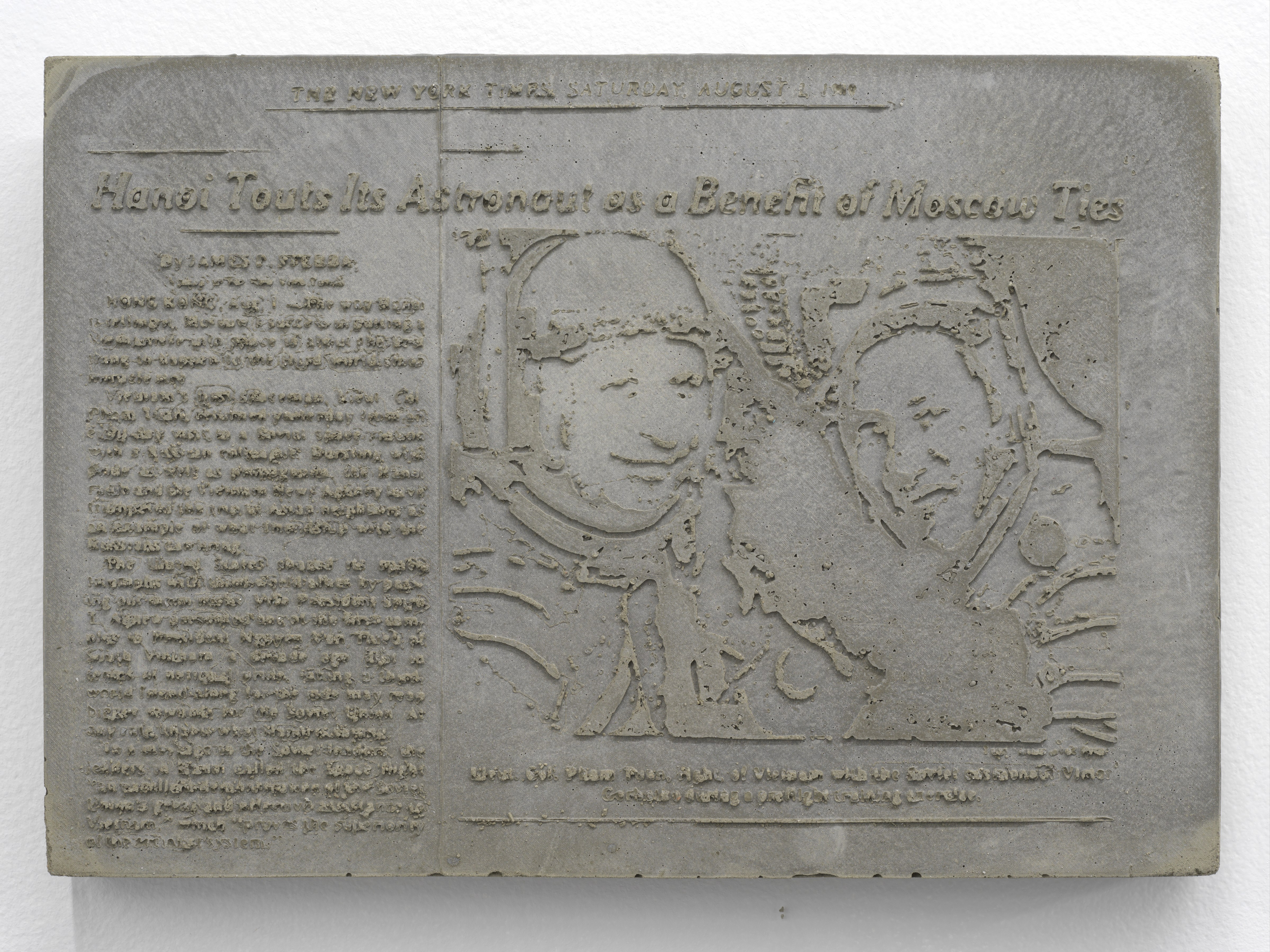 "Image: Photo of a newspaper article from the New York Times cast in concrete. The headline reads, ""Hanoi touts its astronaut as a benefit of Moscow ties,"" The article shows an image of two astronauts wearing space suits and smiling. Image courtesy of the artist."