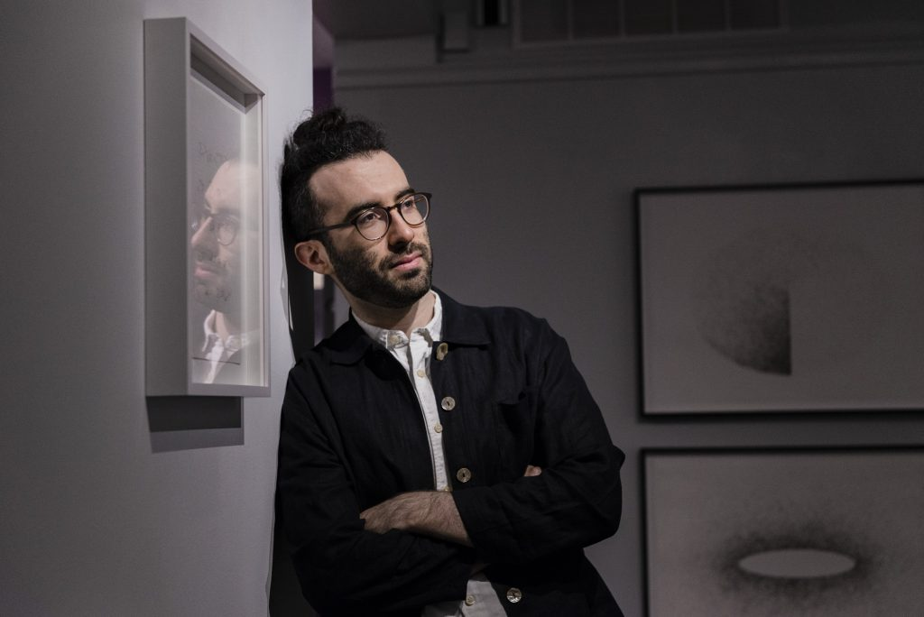 """Image: The artist is leaning against a gallery wall in the LA&M. He is looking off towards the right side of the space, his arms are crossed, and he is wearing a dark button down. He has glasses and a beard. His facial reflection can be seen in a piece that is hanging on the left hand side in a frame. Two """"hair drawings"""" can be seen, out of focus, in the back of the gallery. Photo by Ryan Edmund Thiel."""