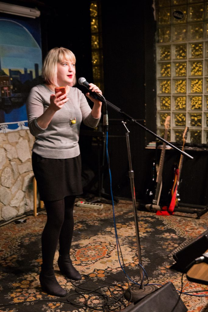Image: Photo of Rosamund Lannin performing on-stage at Miss Spoken at the Gallery Cabaret. Lannin looks out toward the audience (not visible) and speaks into the microphone, while holding a phone in one hand. Lannin wears a grey shirt, black skirt, black leggings, and black boots, and stands on a multi-colored rug. Painted on the stage wall behind the reader is a scene showing Chicago's skyline, as if viewed from behind a stone wall. Also visible in the background are two electric guitars, set to lean toward a black wall with glass-brick windows. Photo by Sarah Joyce. Courtesy of Miss Spoken.