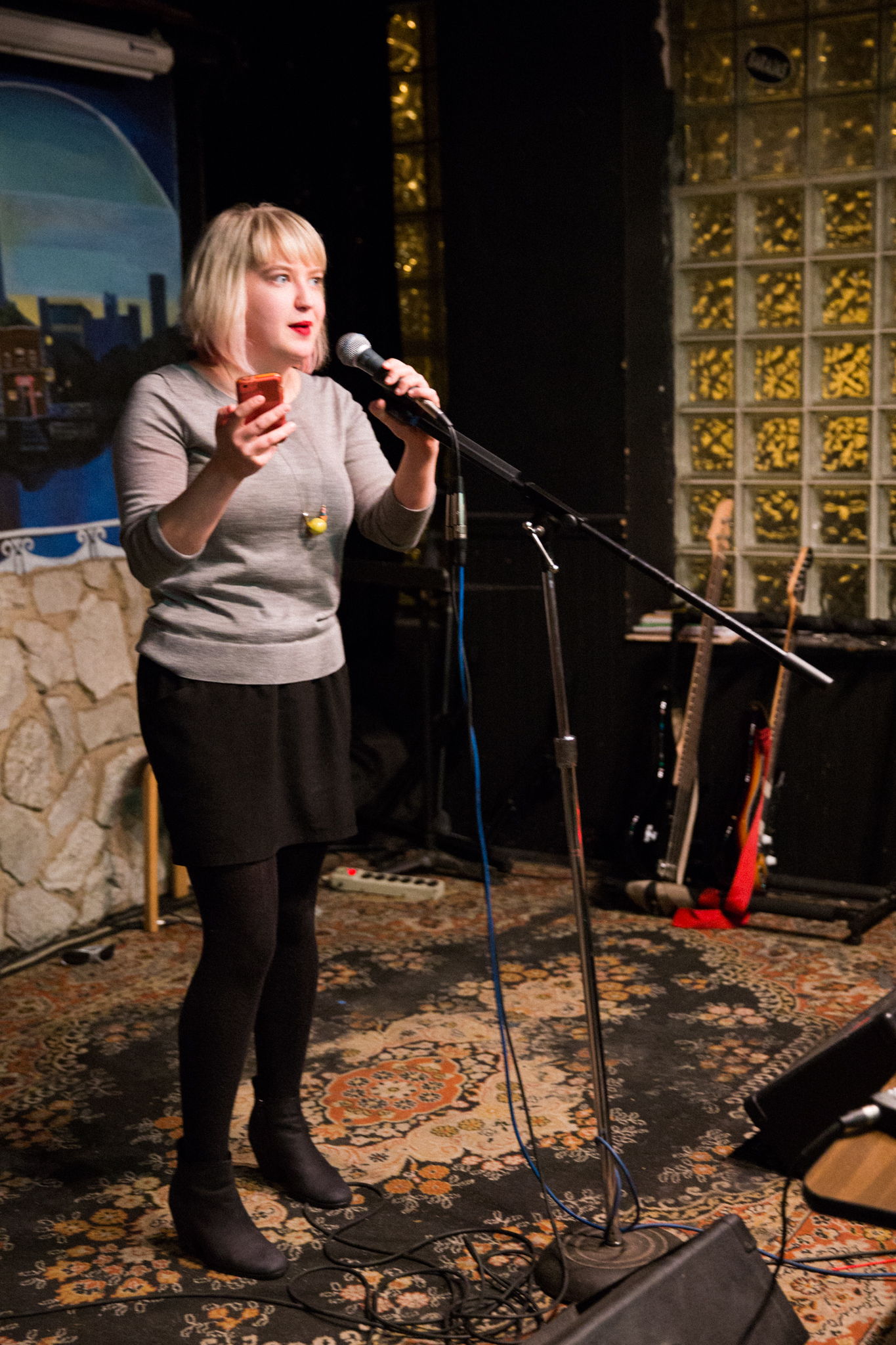 Image: Photo of Rosamund Lannin performing on-stage at Miss Spoken at the Gallery Cabaret. Lannin looks out toward the audience (not visible) and speaks into the microphone, while holding a phone in one hand. Lannin wears a grey shirt, black skirt, black leggings, and black boots, and stands on a multi-colored rug. Painted on the stage wall behind the reader is a scene showing Chicago's skyline, as if viewed from behind a stone wall. Also visible in the background are two electric guitars, set to lean toward a black wall with glass-brick windows. Photo by [Photographer]. Courtesy of Miss Spoken.