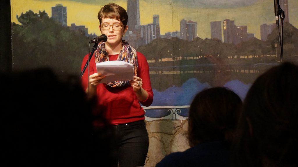 Image: Photo of Nathalie Lagerfeld performing at Miss Spoken at the Gallery Cabaret. The reader stands on-stage, speaking into the microphone and looking down at a set of papers. Lagerfeld wears a red shirt, dark pants, a multi-colored scarf, and glasses. The reader appears in medium-long-shot near the left-center of the frame. Painted on the stage wall behind the reader is a scene showing Chicago's skyline, as if viewed from behind a stone wall. In the foreground, the backs of a few audience members' heads are visible. Photo by Sarah Joyce. Courtesy of Miss Spoken.
