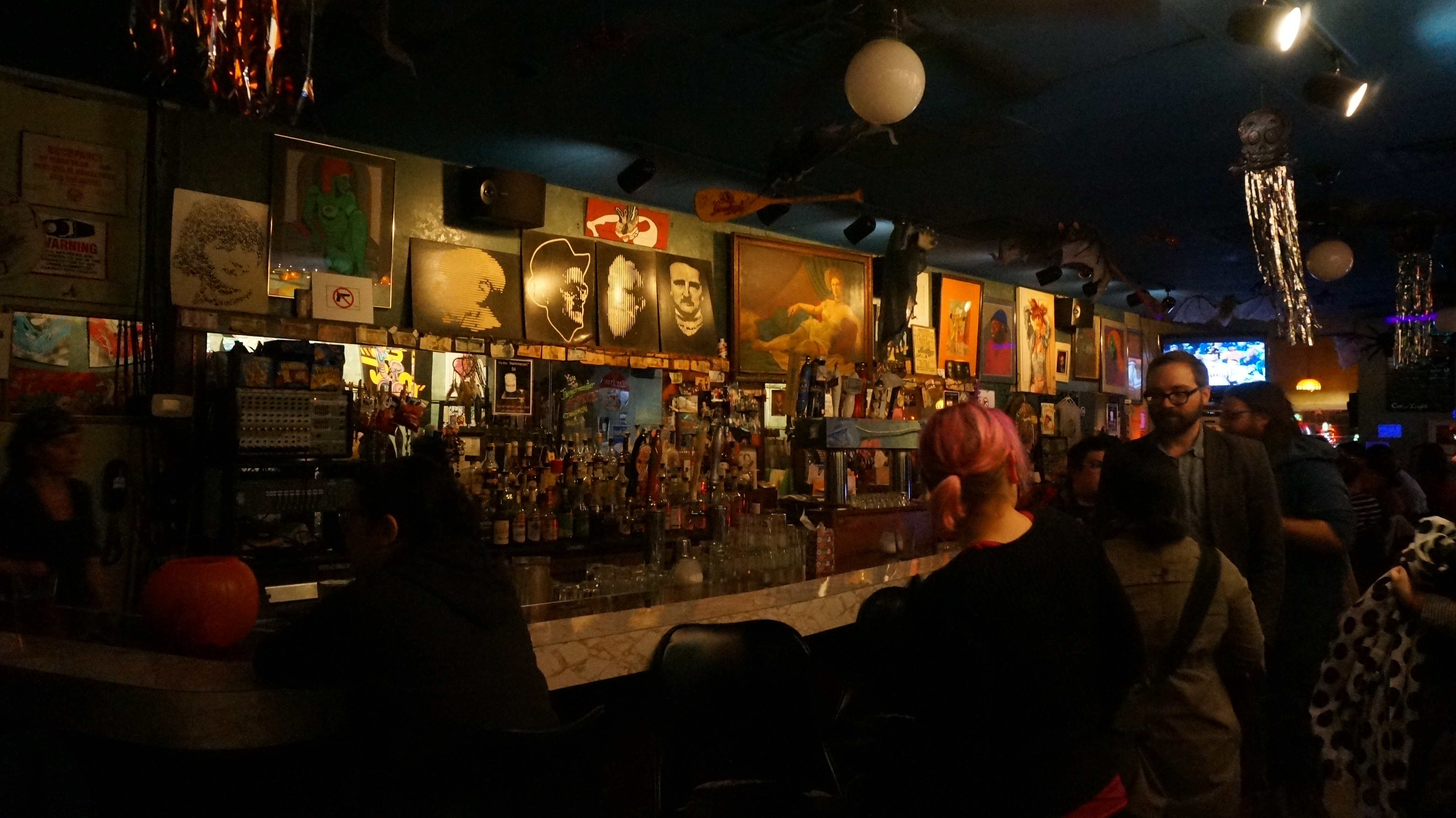 Image: Photo of the bar area at Miss Spoken at the Gallery Cabaret. Lining the wall along the back of the bar area are several drawings, paintings, and photographs. Most images show faces and/or bodies, but are otherwise diverse, reflecting a range of styles, ages, color palettes, etc. Objects like oars and metallic streamers hang from the ceiling. In the foreground, patrons mingle in the dim bar. Photo by [Photographer]. Courtesy of Miss Spoken.
