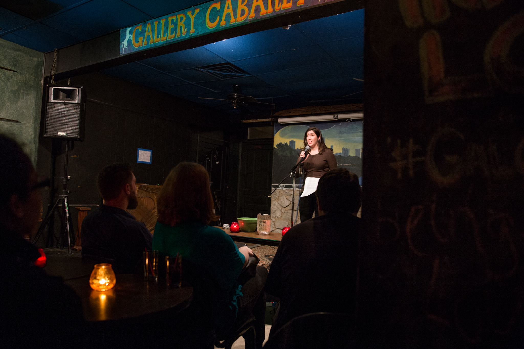 """Image: Photo of [ReaderFirstName ReaderLastName] performing at Miss Spoken at the Gallery Cabaret. The reader stands on-stage, speaking into the microphone and looking out at the audience. One of [ReaderLastName]'s hands grips the microphone and the other holds loose papers. [ReaderLastName] wears a dark shirt and dark pants. The reader appears small near the center of the frame. Painted on the stage wall behind the reader is a scene showing Chicago's skyline, as if viewed from behind a stone wall. In the foreground, the words """"Gallery Cabaret"""" are partially visible at the top of the frame and the backs and sides of some audience members' heads are visible at the bottom; some letters and a hashtag are slightly visible on a foreground wall. Photo by [Photographer]. Courtesy of Miss Spoken."""