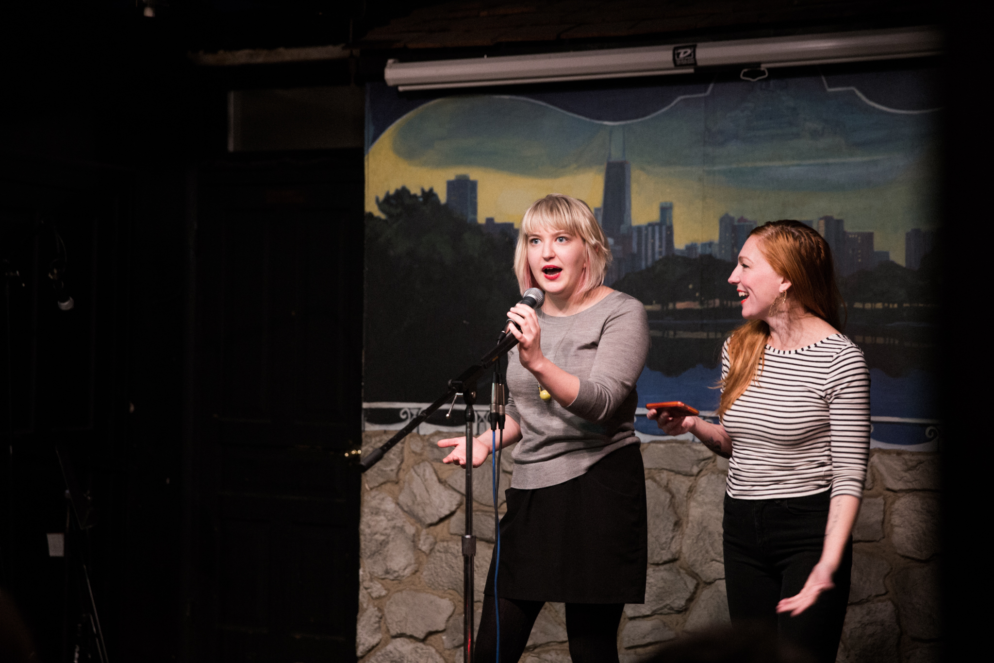 Image: Photo of Rosamund Lannin (left) and [ReaderFirstName ReaderLastName] standing on-stage at Miss Spoken at the Gallery Cabaret. Both appear in medium[-long?]-shot on the right side of the frame. Lannin looks out toward the audience (not visible) and speaks into the microphone, while [ReaderLastName] smiles and looks at Lannin. Lannin wears a grey shirt, black skirt, and black leggings. [ReaderLastName] wears a black and white striped shirt and black pants. Painted on the stage wall behind the readers is a scene showing Chicago's skyline, as if viewed from behind a stone wall. Photo by [Photographer]. Courtesy of Miss Spoken.
