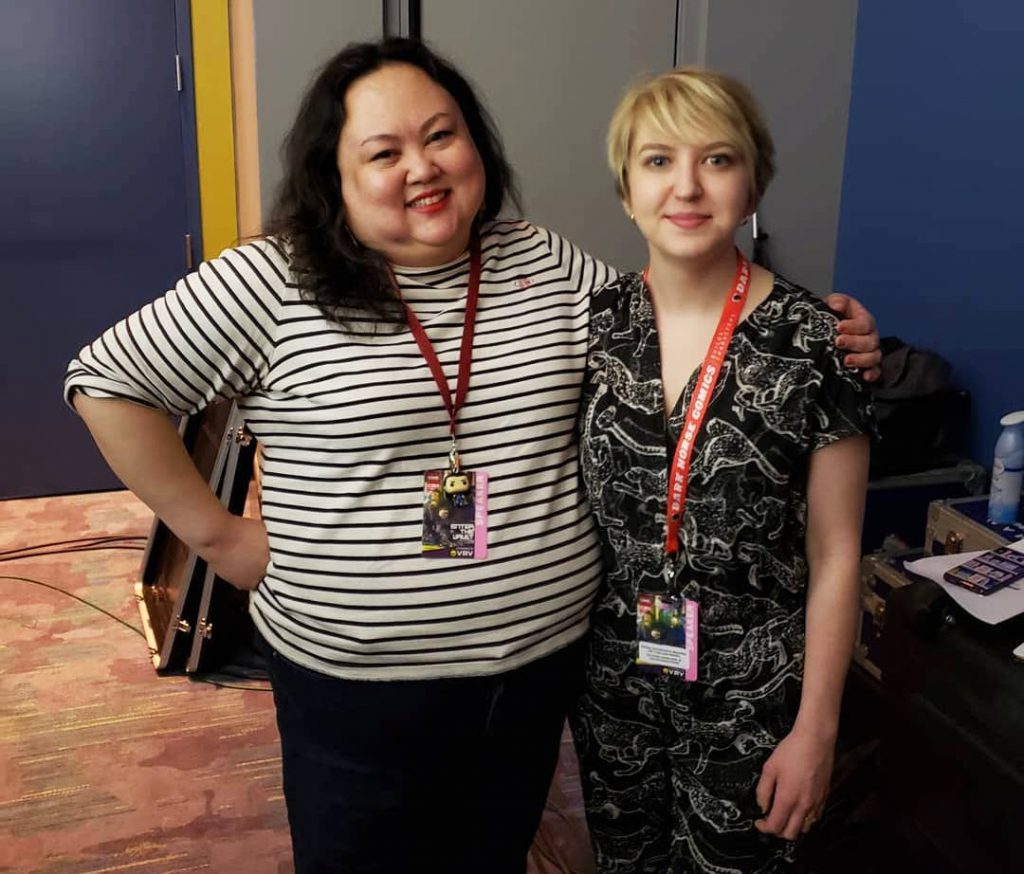 "Image: Jasmine Davila (left) and Rosamund Lannin (right) stand together backstage at C2E2 for Cards Against Humanity Theater, smiling for the camera. Davila wears a white and black striped shirt and black pants, and Lannin wears a patterned black and white jumper. Both wear red lanyards around their necks and badges that read ""Speaker."" Davila has one arm around Lannin's shoulders. Around them backstage are A/V equipment cases and miscellaneous objects. Courtesy of Miss Spoken."