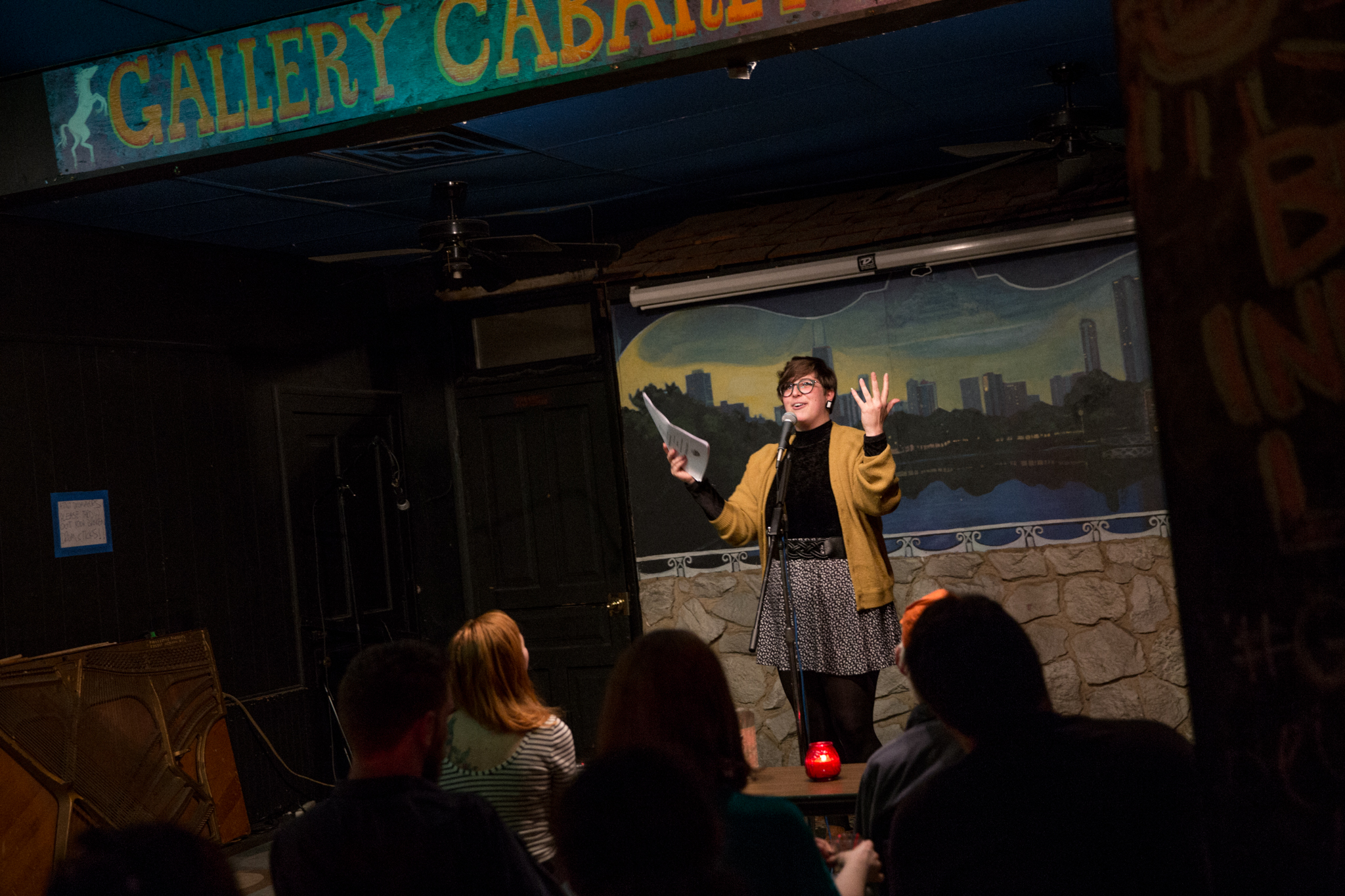 "Image: Photo of Brittany Meyer performing at Miss Spoken at the Gallery Cabaret. The reader stands on-stage, smiling and speaking into the microphone while looking out at the audience. Meyer's hands are raised in expression; one hand holds loose papers and the other is open. Meyer wears a mustard-gold cardigan open over a black turtleneck, a dark patterned skirt over dark leggings, and glasses. The reader appears small near the center of the frame. Painted on the stage wall behind the reader is a scene showing Chicago's skyline, as if viewed from behind a stone wall. In the foreground, the words ""Gallery Cabaret"" are partially visible at the top of the frame and the backs of some audience members' heads are visible at the bottom. Photo by  Sarah Joyce.  Courtesy of Miss Spoken."
