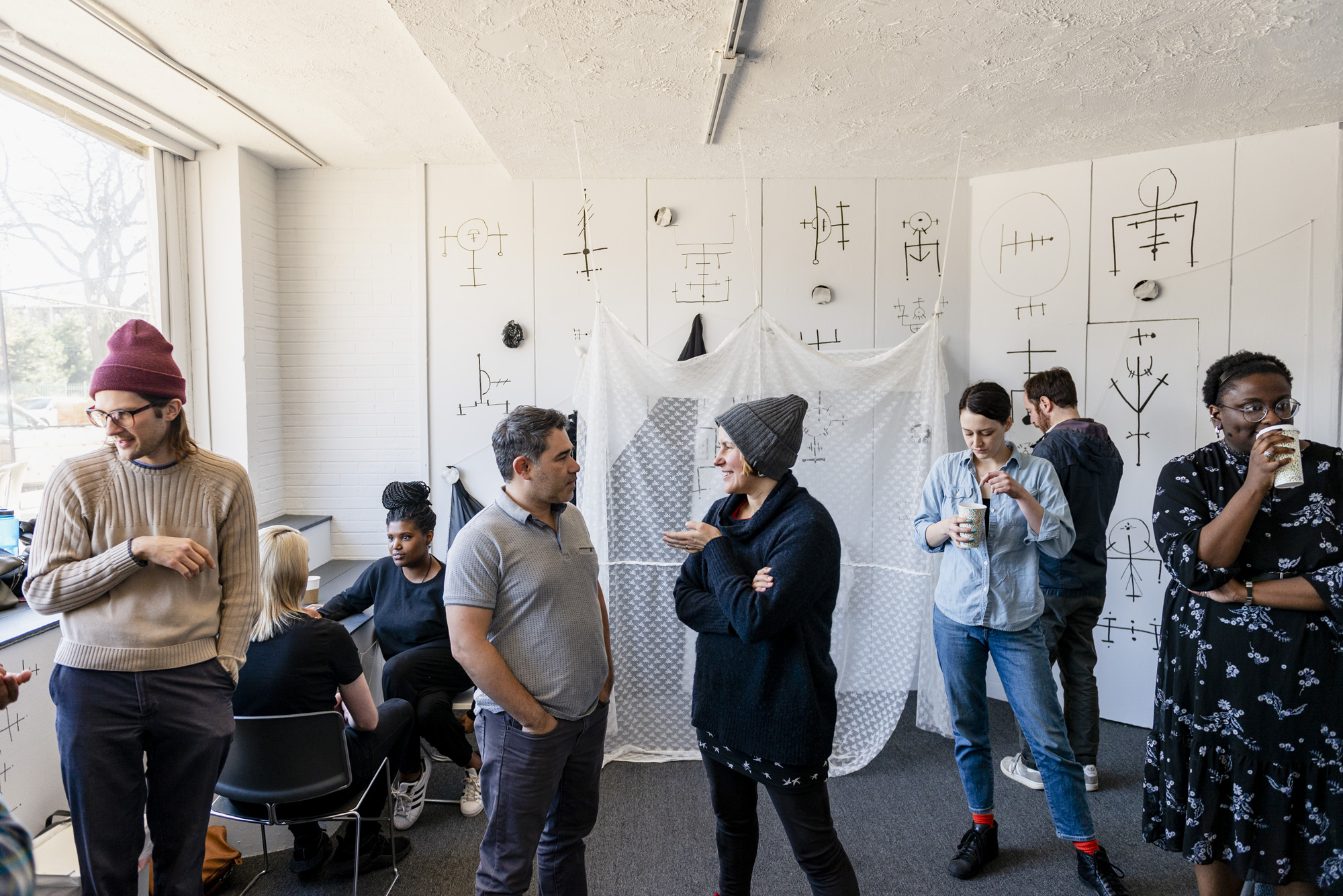 Image: A group of people standing inside Roman Susan. Zuri Washington (far right) transformed the space by painting black sigils on the white walls and adding fiber elements. Event co-curator Adia Sykes (back left) is sitting at a table with event attendee and facilitating a tarot card reading. Photo by Ryan Edmund.