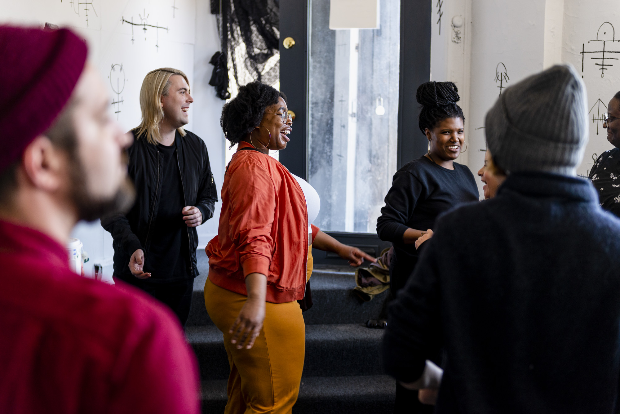 Image: Participants at Root & Rise partaking in the euphoric dance party at Roman Susan. Some are in focus and others are out of focus, but all are dancing and smiling. Peeking out from behind their heads are the black hand painted sigils on the gallery walls. Photo by Ryan Edmund.