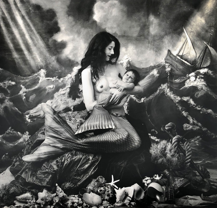 Image: A black and white photograph of a woman wearing a mermaid tail, seated on a seashell-ladened formation. She is bare-chested holding a baby, also adorned with a mermaid tail. Behind them is a painted backdrop depicting a sea full of waves and a ship off to the right. A Mermaid's Tale, NM, 2018 © Joel-Peter Witkin / image courtesy Catherine Edelman Gallery, Chicago.