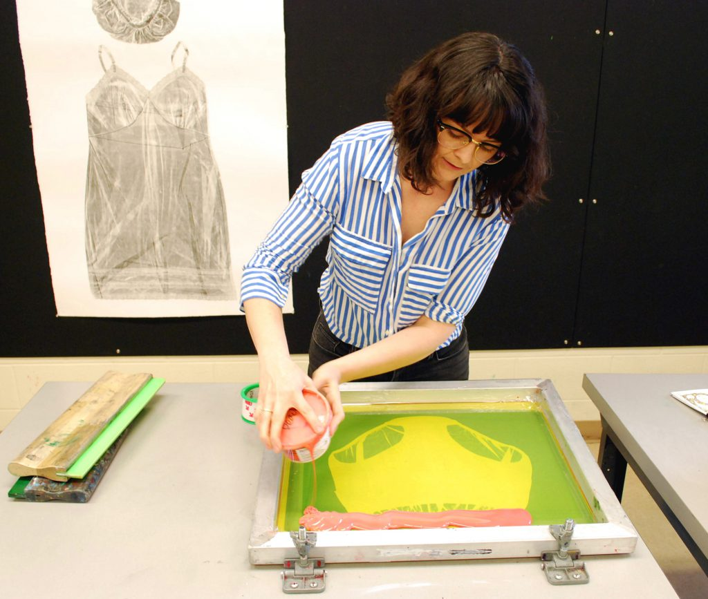 Image: Guen Montgomery pours neon pink paint onto a screenprinting screen with an image of women's underpants on it. Pinned behind her on a black corkboard is a gray collagraph print of a woman's shower cap and nightgown on white paper. Photo by Jessica Hammie.
