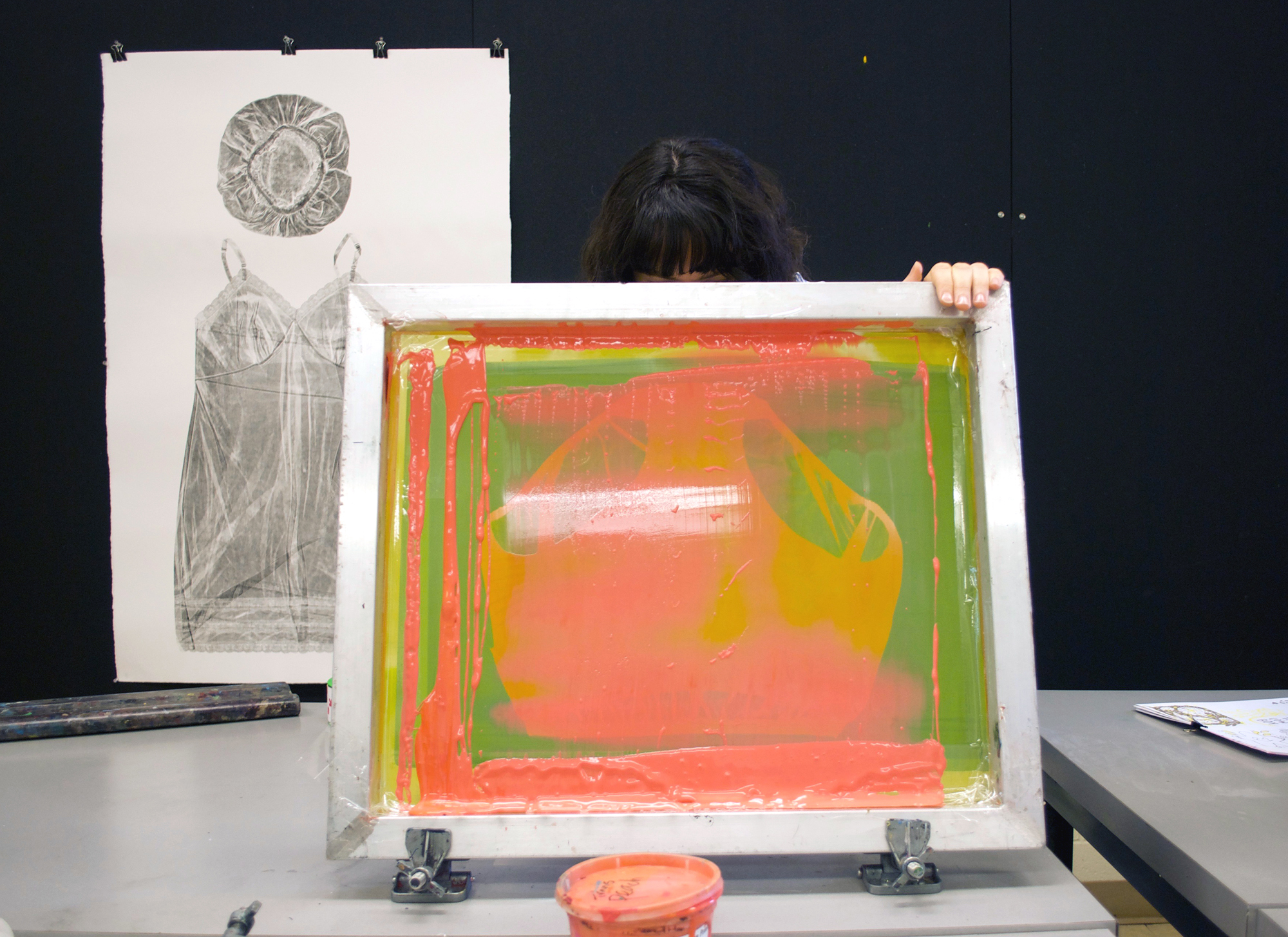 Image: Guen Montgomery holds a screenprinting screen up, exposing the neon pink paint-covered screen to the camera. The top of her head is visible above the screen. Pinned behind her on a black corkboard is a gray collagraph print of a woman's shower cap and nightgown on white paper. Photo by Jessica Hammie.