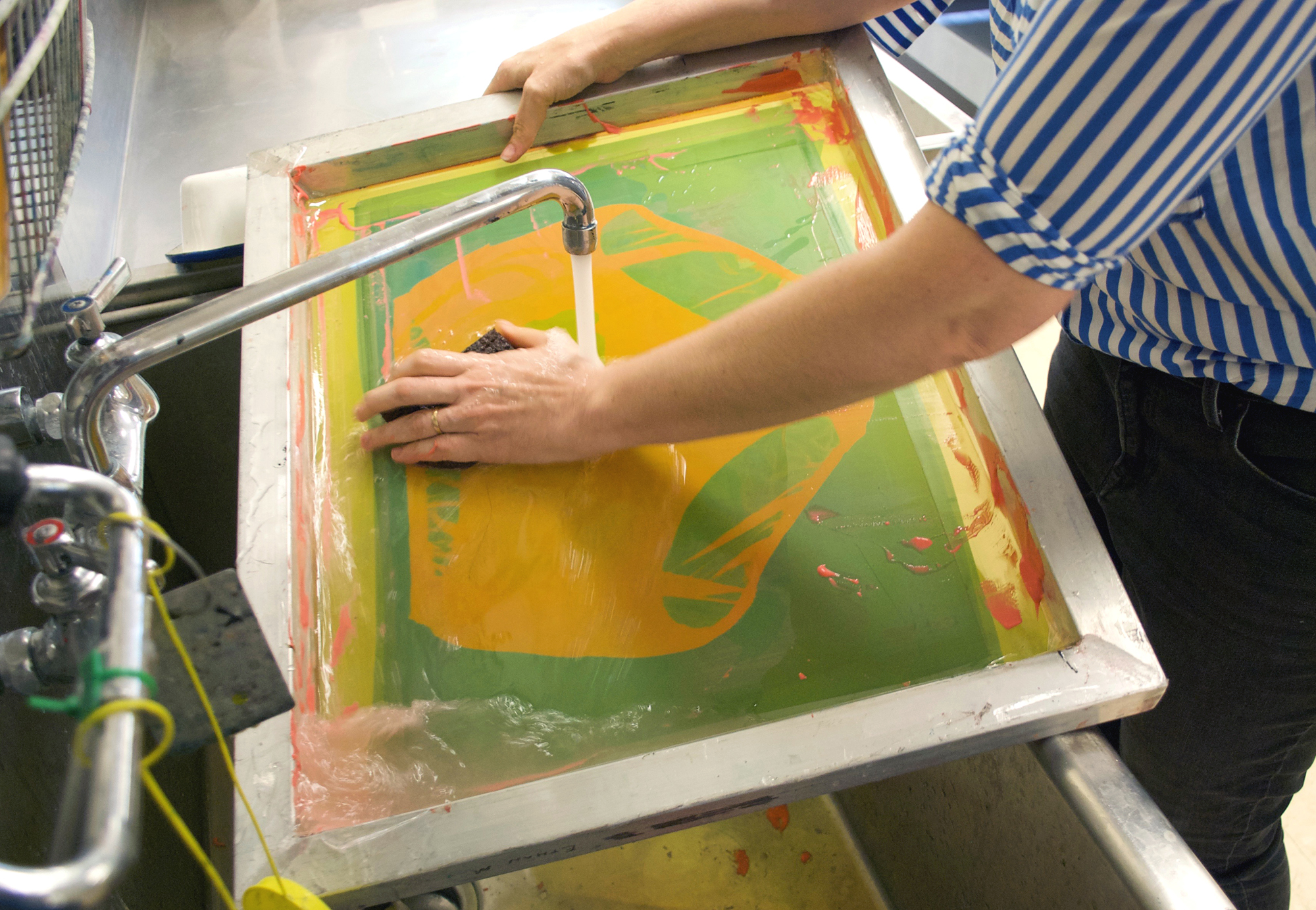 Image: Guen Montgomery washes a screenprinting screen in a small sink. Her left hand uses a sponge to wash of neon pink paint as water pours out of a faucet and onto the screen. Photo by Jessica Hammie.