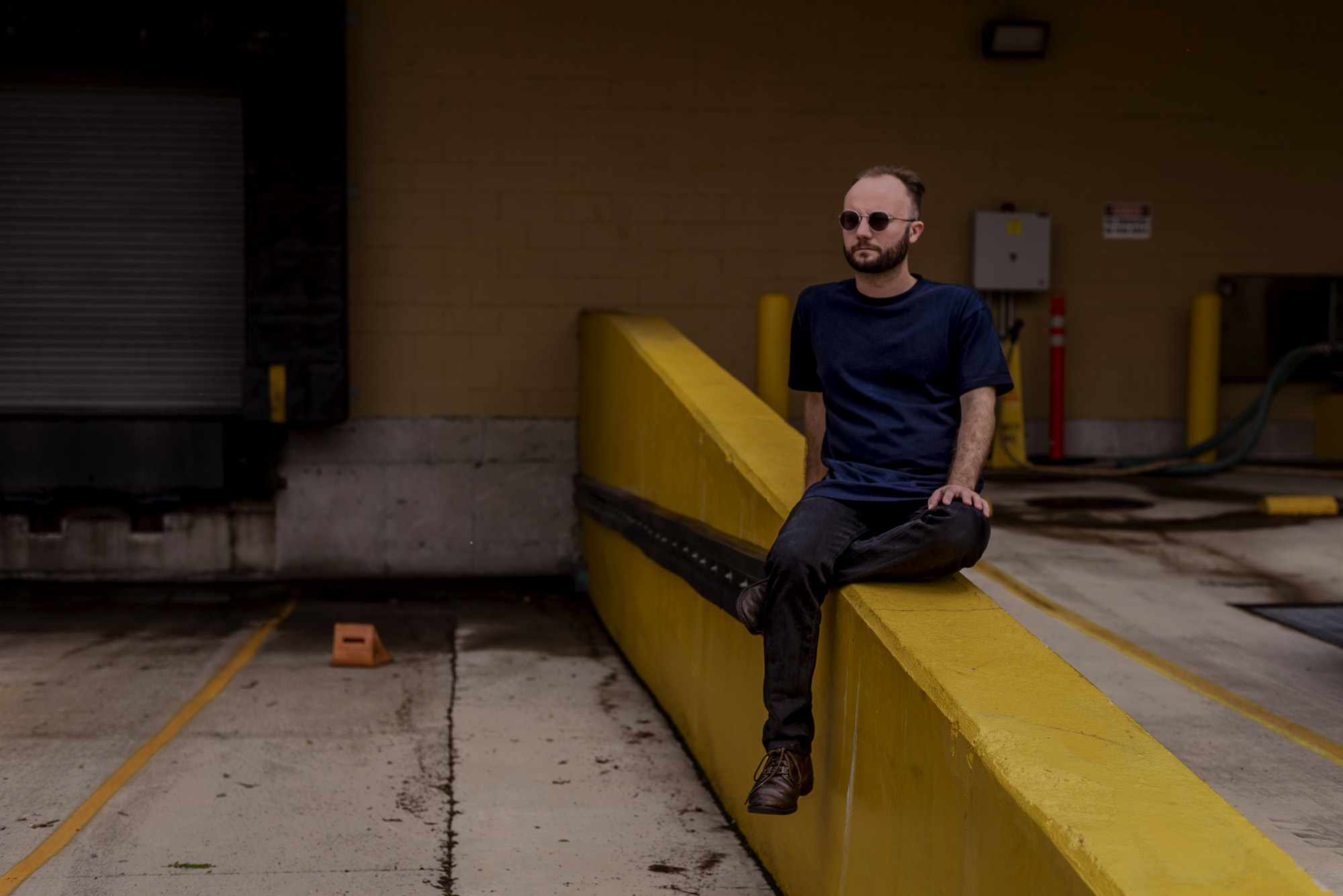 Featured Image: Elliot J. Reichert sits, legs crossed, on a yellow concrete platform in what appears to be the exterior of a loading dock. He's looking out to the left of the frame. Photo by Ryan Edmund.