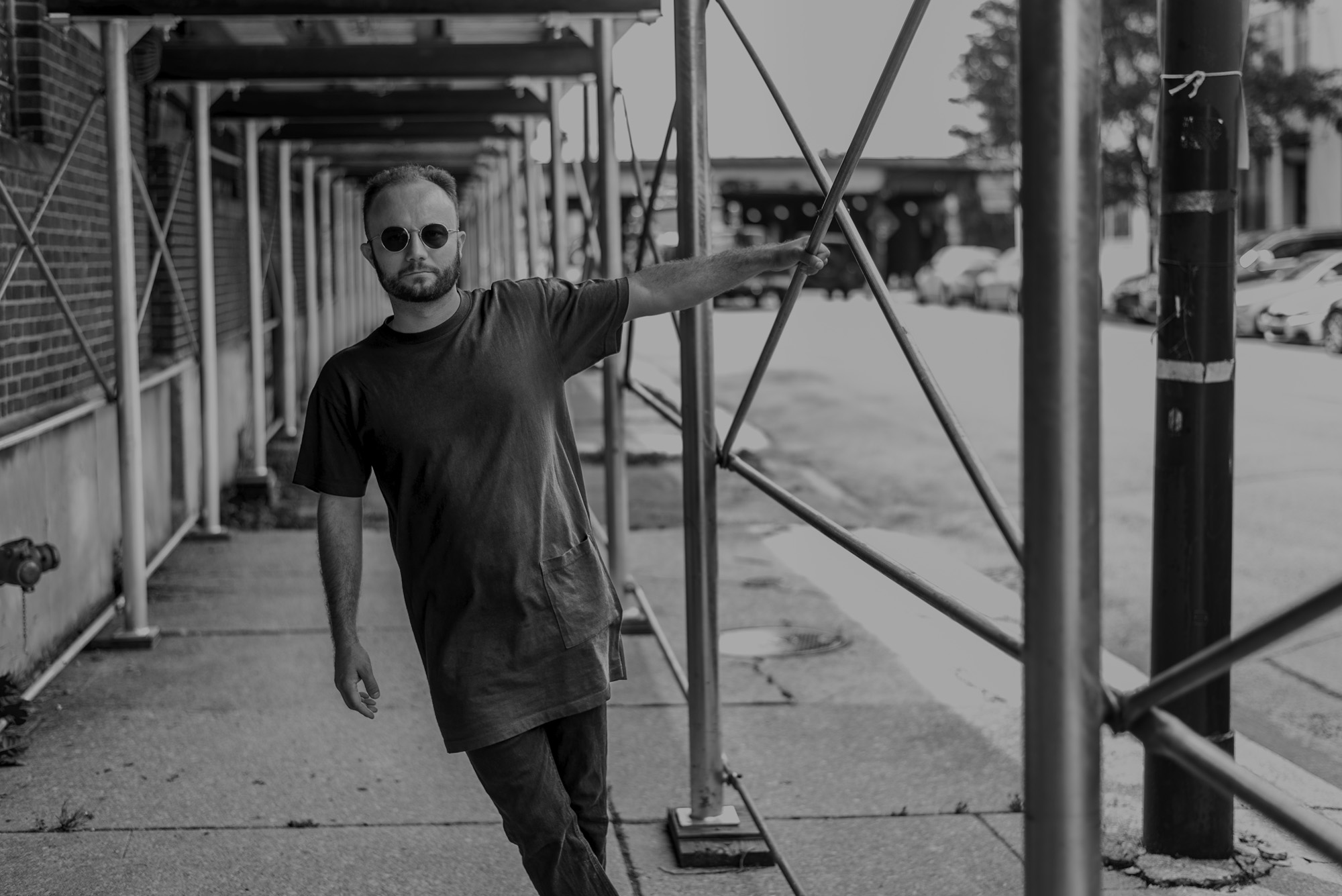 Image: Elliot stands under scaffolding along a brick building, with the street to the right. One hand holds onto a post on the scaffolding, and he's leaning out to the left towards the frame. Photo is in black and white. Photo by Ryan Edmund.