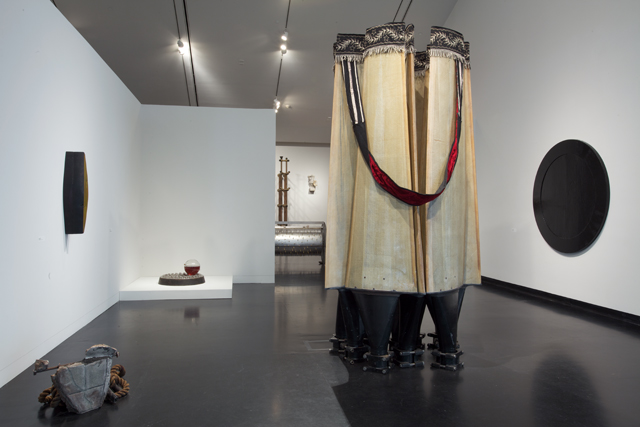 Image: Terry Adkins Recital, installation view, Tang Museum, 2012. The image shows several of Adkins' sculptural works. A large one and a much smaller one are free-standing on the floor of the gallery, two are mounted on the walls at either side of those sculptures, and several can be seen in the background, on pedestals and in other sections of the exhibition space. Photo courtesy of the Mary and Leigh Block Museum, Northwestern University.