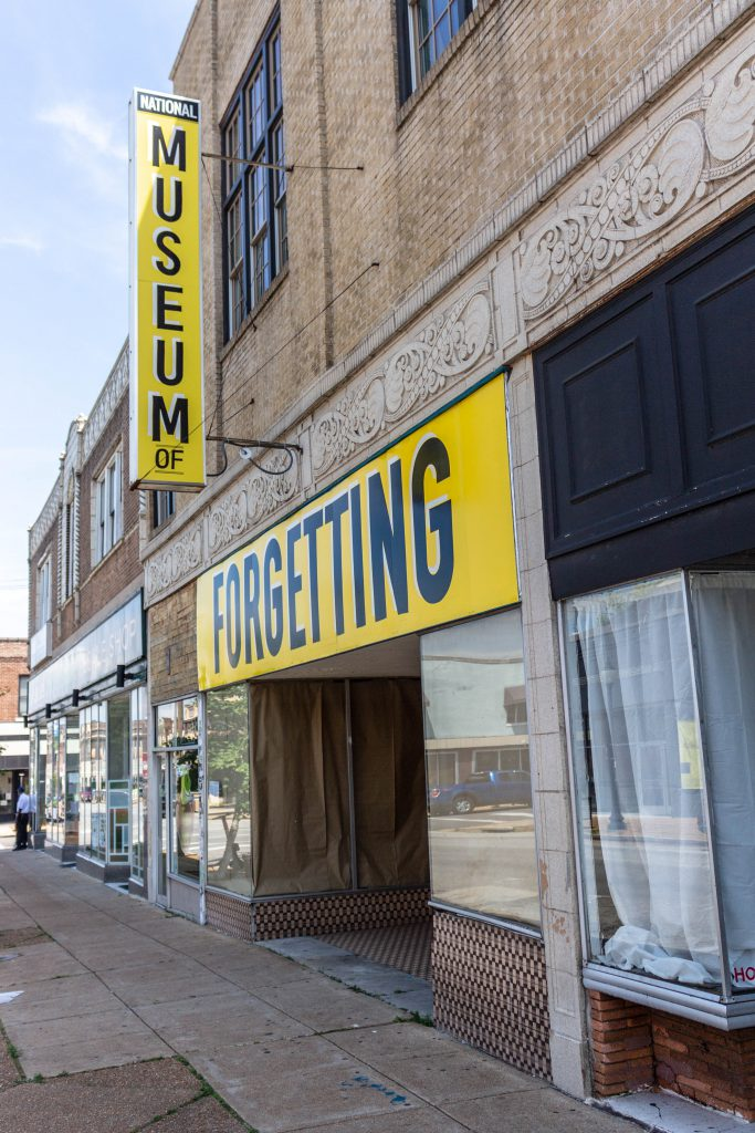 "Image: Joseph del Pesco and Jon Rubin, Monuments, Ruins and Forgetting; 2019. Installation with changing signpainting. A vacant storefront has two large yellow sign that together reads ""The National Museum of Forgetting."" Photo by Shabez Jamal."