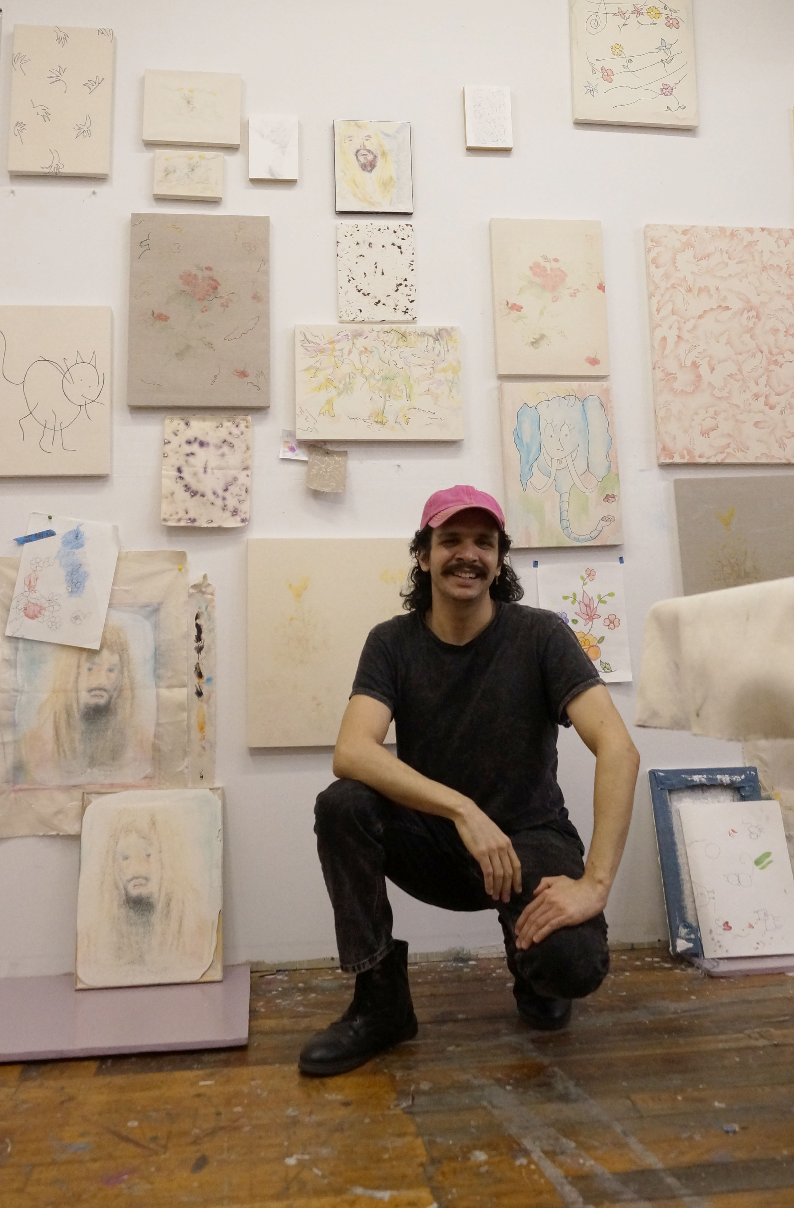 Image: Alejandro Jiménez-Flores crouching down smiling in front of his artwork. He is wearing dark clothing and a pink hat.