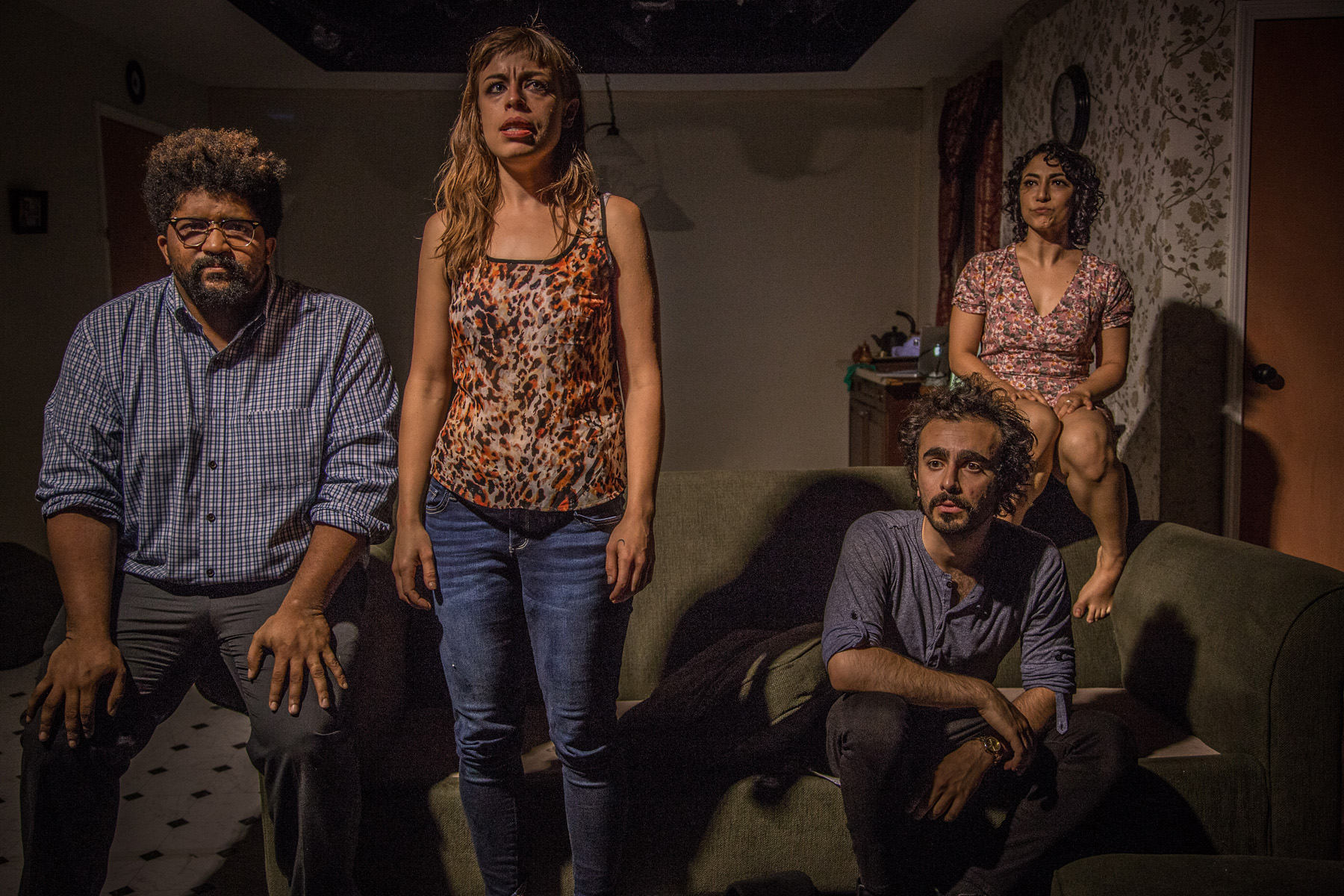 """Featured image: The cast of """"KISS."""" From left to right; director Monty Cole sits on the arm of an olive green couch, with his hands on his thighs facing us. He wears glasses and a blue checked shirt. Cassidy Slaughter-Mason stands in front of the couch arms at her side. She looks up and to the right. She wears a leopard print tank top and blue denim jeans. Her shadow grazes Salar Ardebili who sits on the couch staring out to the left. He wears a blue shirt and black pants. Arti Ishak sits behind him wearing a pink and brown floral dress, looking out to the left. There is a hanging lamp behind them, a door to their left, and a kitchen sink behind Ishak. Image courtesy of Austin D. Oie."""
