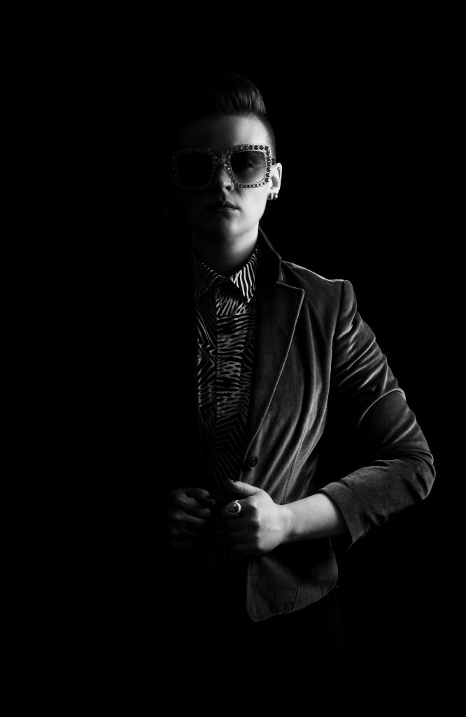 Image: Chelsea Fiddyment as Sir Elton Brawn. In this black-and-white medium shot, Fiddyment looks directly at the camera, with half of Fiddyment's body hidden in shadow. Fiddyment wears sunglasses that are rimmed in large rhinestones. Fiddyment's hands grip the dark velour jacket, open at the abdomen. Fiddyment wears a black and white patterned shirt, buttoned all the way up, and dark bottoms. Photo by Trainman Photography. Courtesy of the artist.