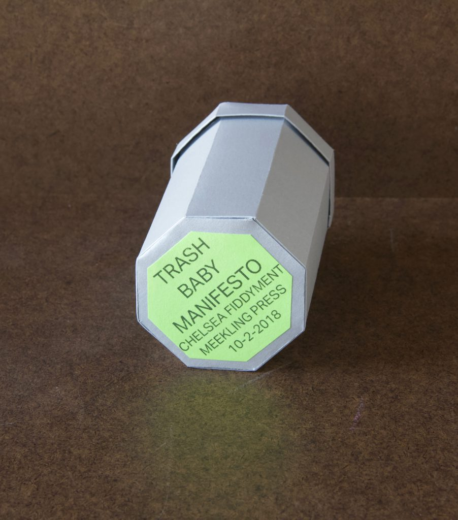 """Image: A photo of """"Trash Baby Manifesto,"""" a book by Chelsea Fiddyment, 2018. The book's casing looks like a trashcan — octagonal at the base and top, with a lid. It is made out of thin white cardboard. The focal point of the image is the bottom of the trashcan, where a light green octagonal sticker reads, in all capital letters, """"Trash Baby Manifesto, Chelsea Fiddyment, Meekling Press, 10-2-2018."""" The book sits on a dark surface. Photo by Meekling Press. Courtesy of the artist."""