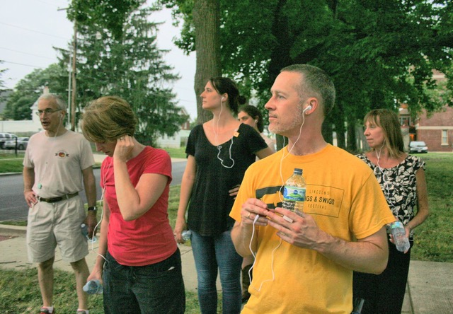 Image: Enos Park Uncovered: Audio-Walk created by Astrid Kaemmerling in 2017. Participants walking the neighborhood while listening to the audio-walk being led by Astrid Kaemmerling, Location: Enos Park, IL. Photo by Job Conger.