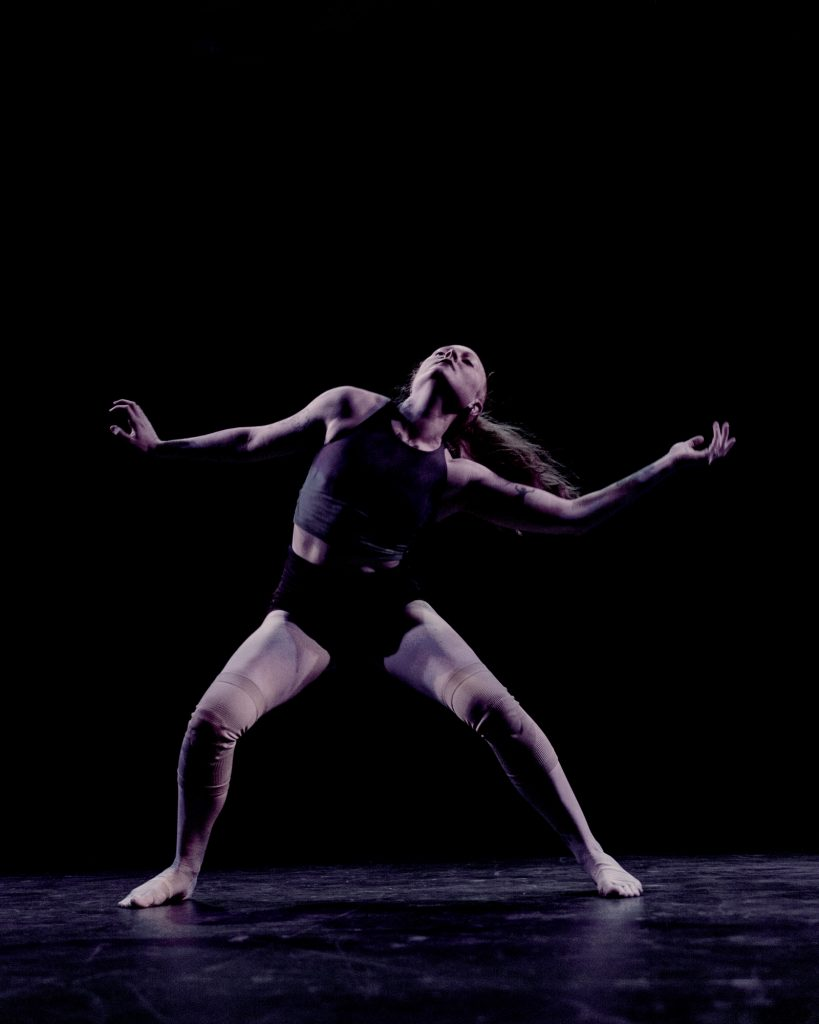 Image: A dancer (Julia Cox) dressed in a fitted top, shorts, and knee-wraps is in motion on a dark stage; she leans back, gesturing widely with her arms and legs splayed. Photo by Ryan Edmund.