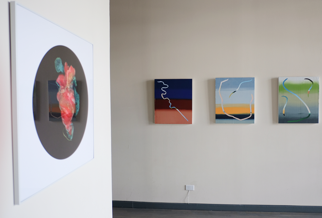 Image: A gallery with beige walls. Left, a square frame containing Kelvin Burzon's LATEX: Heart: a white drop containing a black circle containing a photograph of dyed latex and condoms approximating the shape of a heart. Right, on another wall and hung five feet off the ground,  Roberto Jamora's trio, from left to right, Bayou St. Malo, Lake Borgne, and Manila Plaza. Image courtesy of FLXST Contemporary.